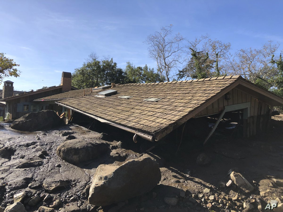In this photo provided by Santa Barbara County Fire Department, mudflow, boulders, and debris from heavy rain runoff from early Tuesday reached the roof of a single story home in Montecito, Calif., on Jan. 10, 2018.