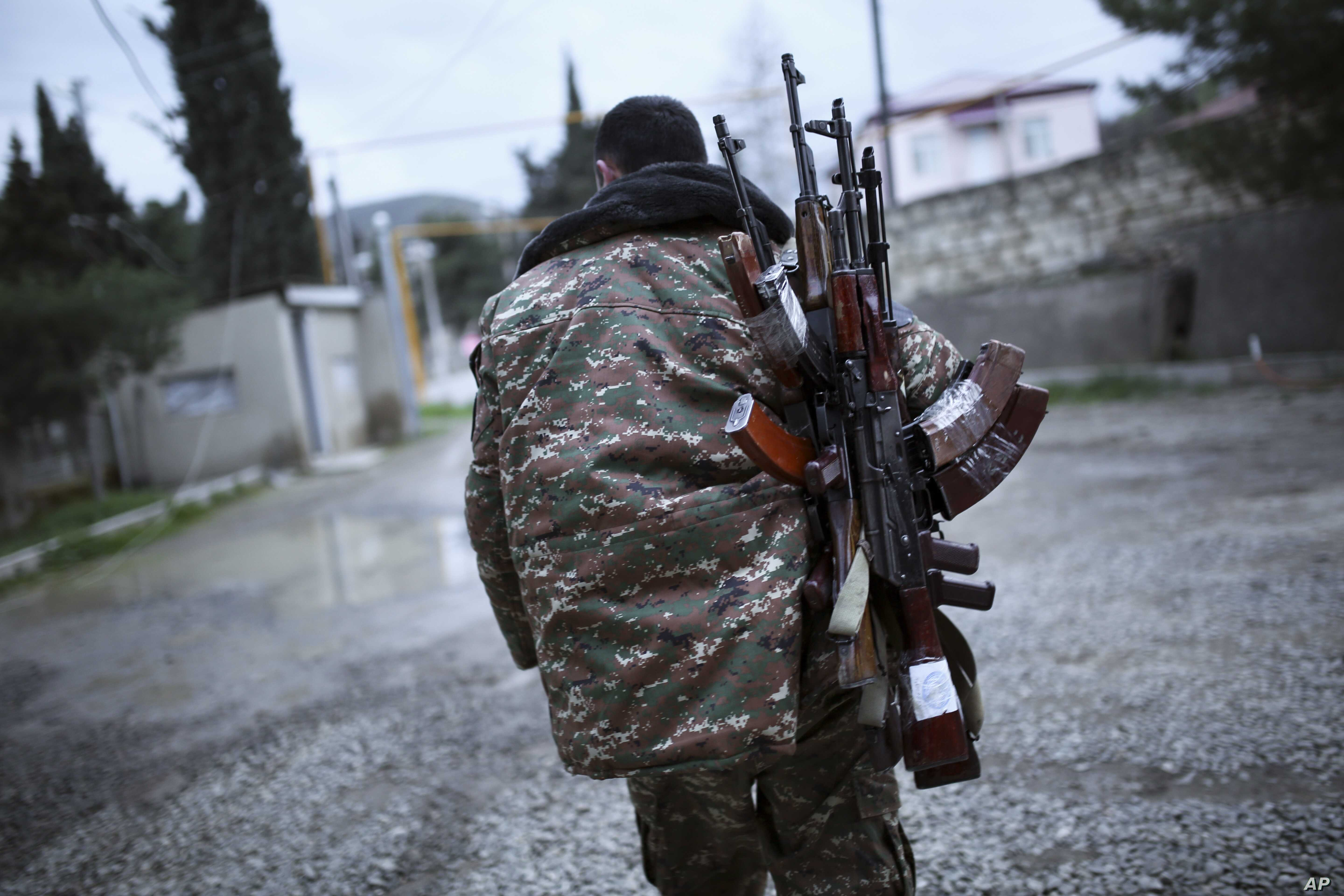 An ethnic Armenian fighter carries Kalashnikov machine guns to his comrade-in-arms at Martakert province in the separatist region of Nagorno-Karabakh, Azerbaijan, Monday, April 4, 2016.