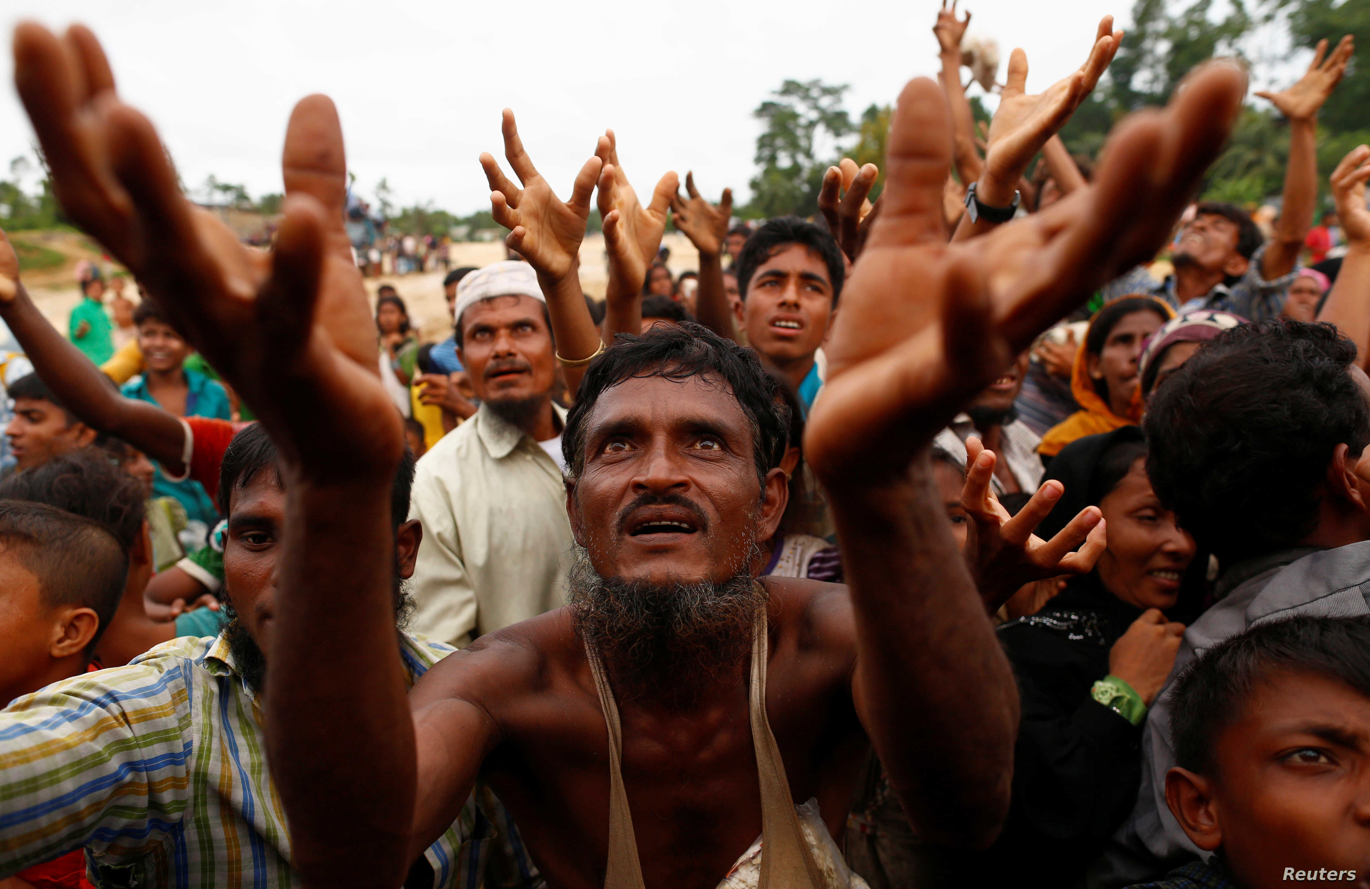 Rohingya refugees stretch their hands to receive food distributed by local organizations in Kutupalong, Bangladesh, Sept. 9, 2017.