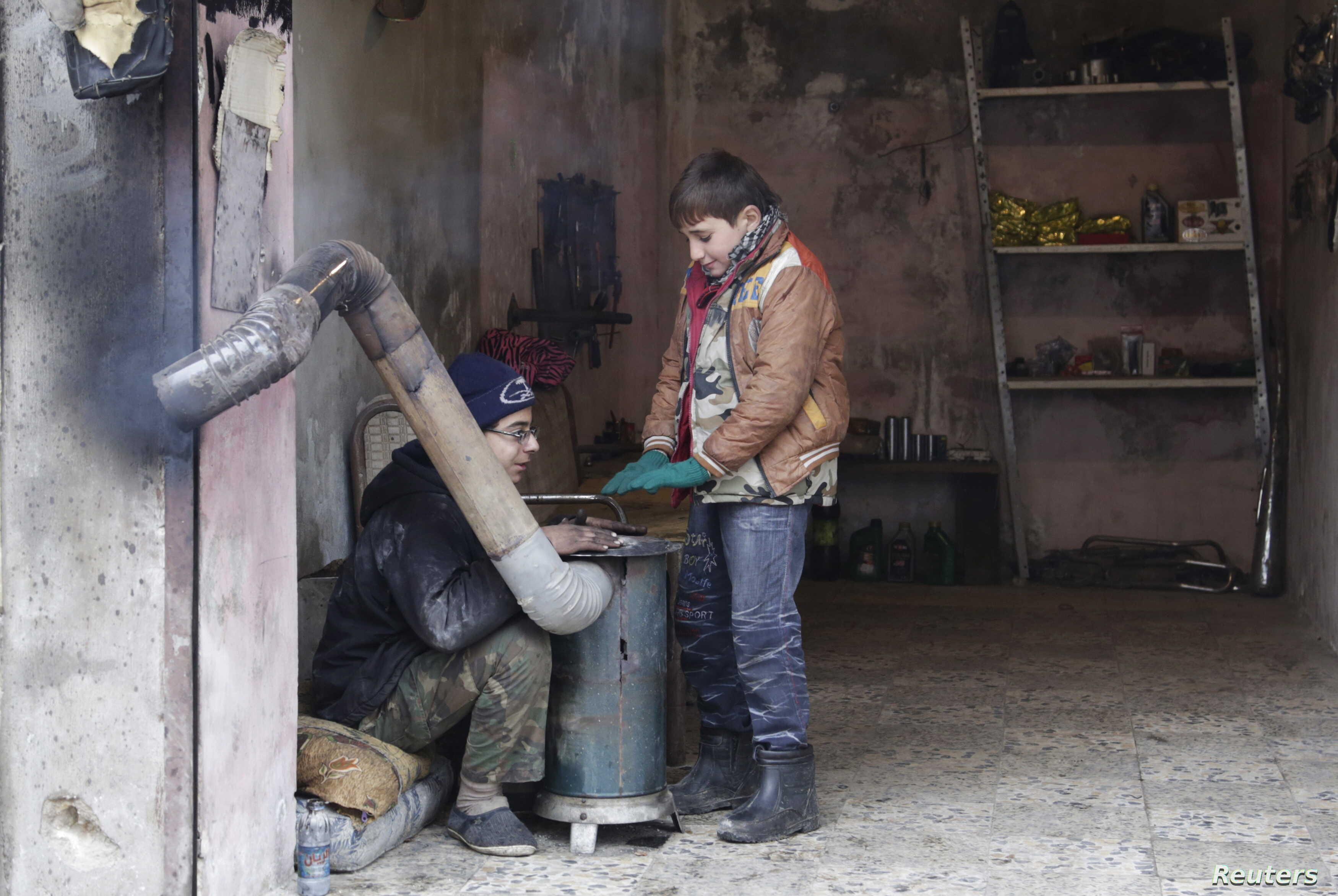 FILE - Boys warm themselves around a heater inside a shop during cold weather in the rebel-controlled area of Maaret al-Numan town in Idlib province, Syria, Jan 4, 2016.