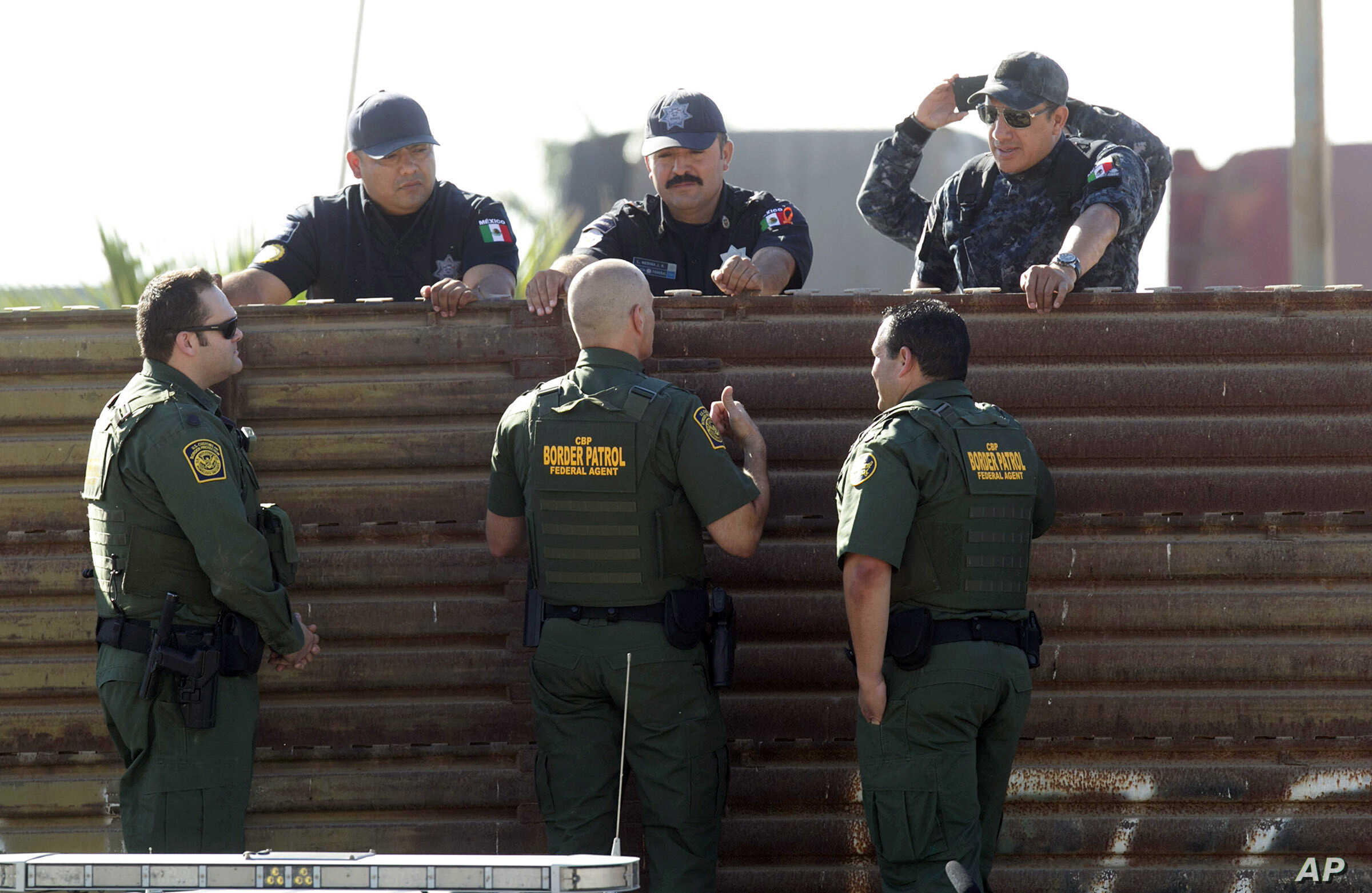 FILE - U.S. Customs and Border Protection's acting deputy commissioner Ronald Vitiello, center foreground, and two other CBP agents, talk over the primary fence to their Mexican Federal Police counterparts in Tijuana, Mexico, Oct. 26, 2017, in San ...