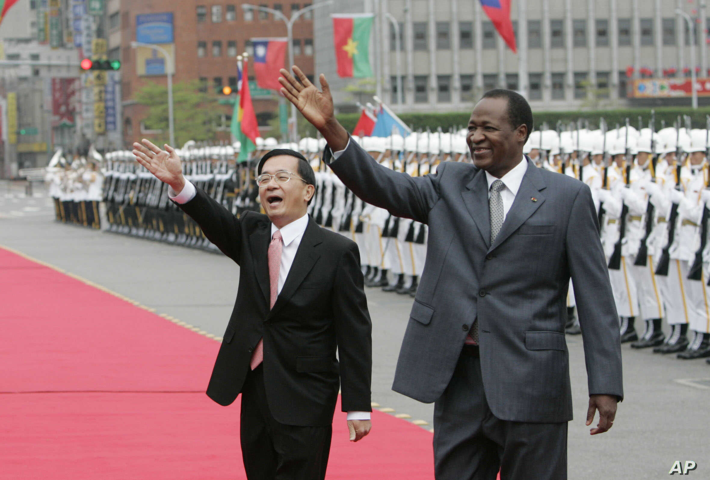 FILE - Taiwan's then-president, Chen Shui-bian, left, and Blaise Compaor, who was then president of Burkina Faso, wave to well-wishers during an honor guard review, Nov. 20, 2006, in front of the Presidential Office in Taipei, Taiwan. Burkina Faso ha...