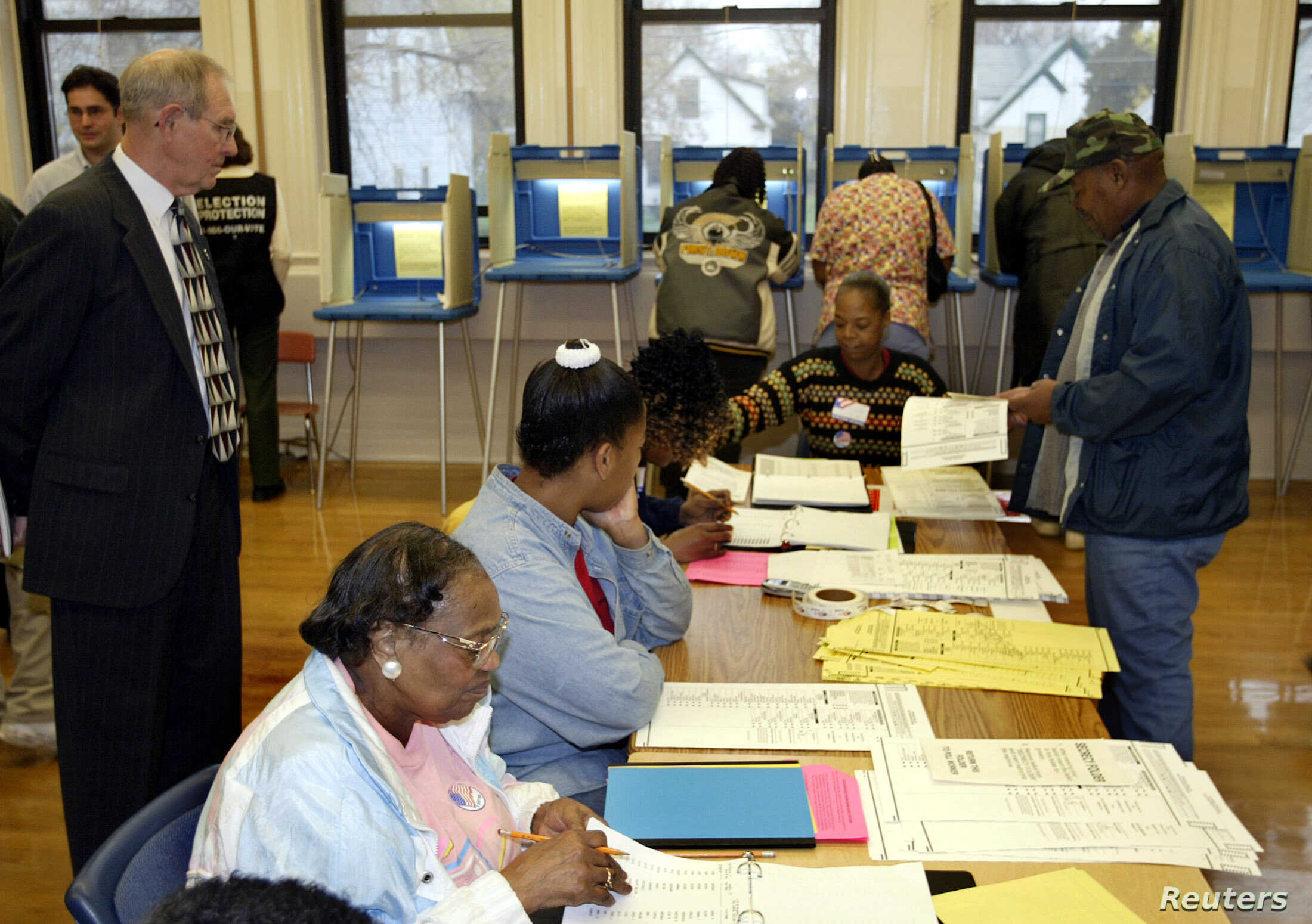 FILE - John Spindler, a lawyer representing the Republican National Committee, watches as poll workers issue a ballot to Tommie Rash, right, at Hopkins Street School on the north side of Milwaukee, Wis., Nov. 2, 2004.