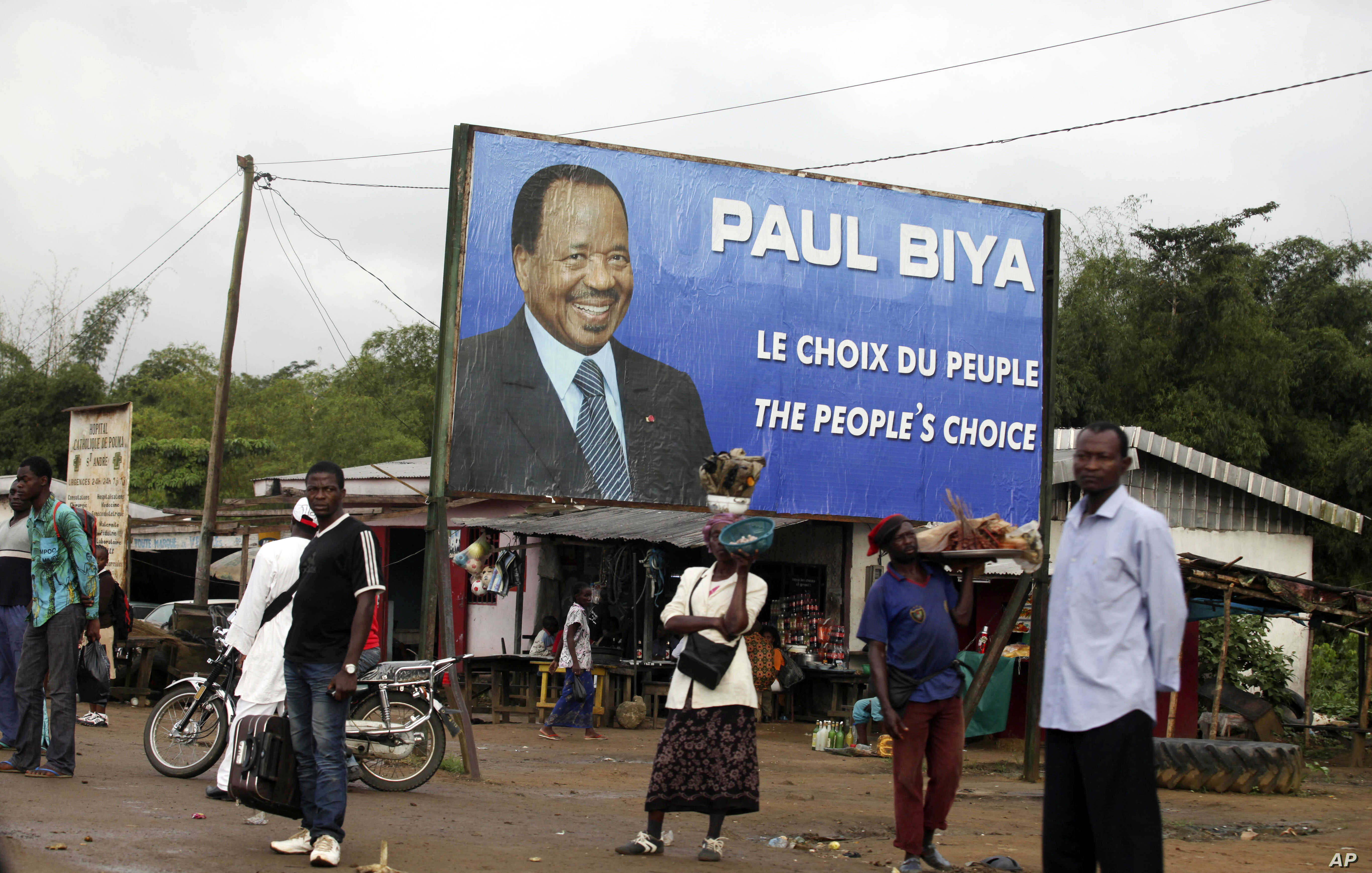 FILE - Residents wait for transportation under a campaign poster for Cameroon President Paul Biya in Doula, Cameroon, Oct. 6, 2011.