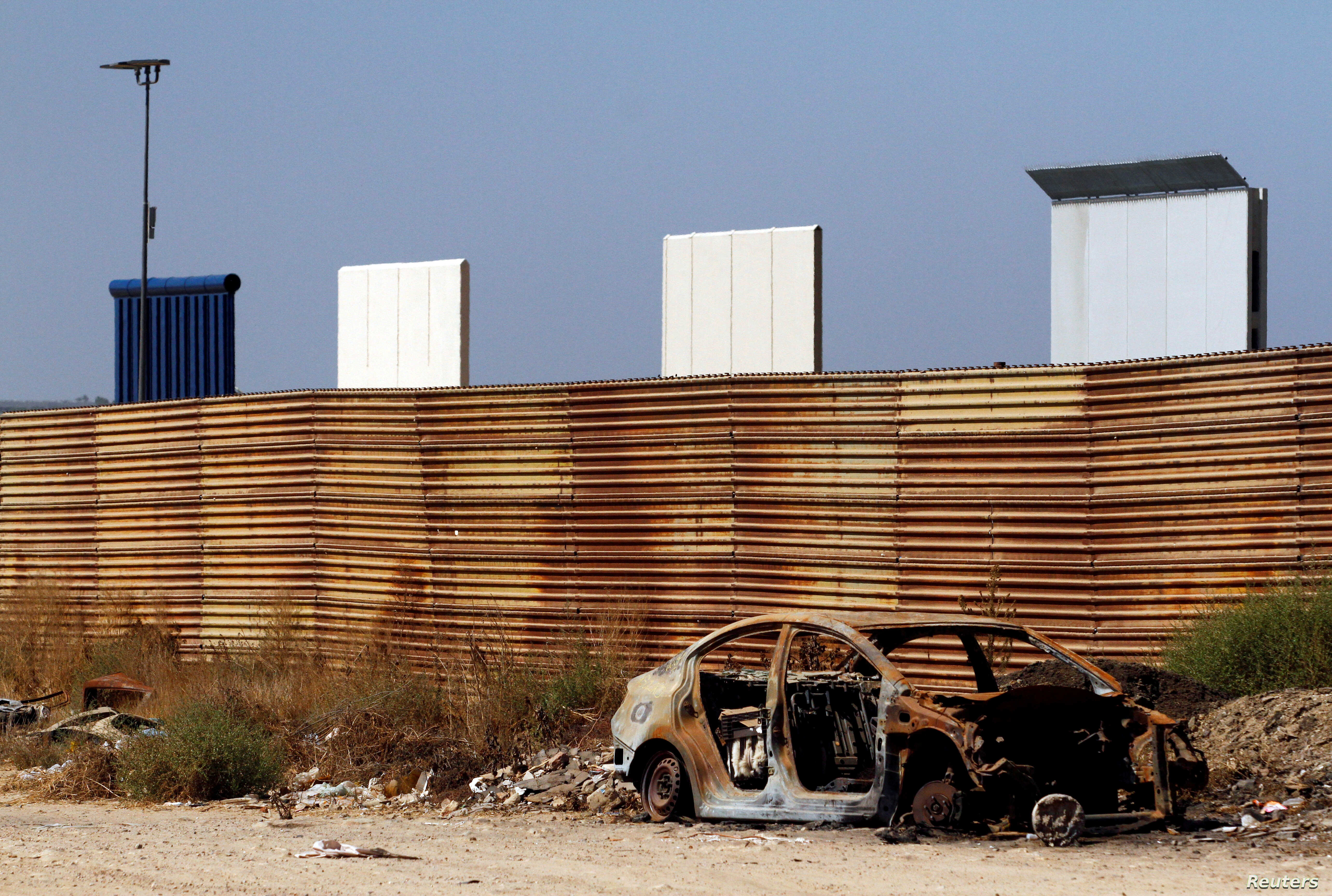 FILE: Prototypes for U.S. President Donald Trump's border wall with Mexico are seen behind the current border fence in this picture taken from the Mexican side of the border in Tijuana, Oct. 12, 2017.