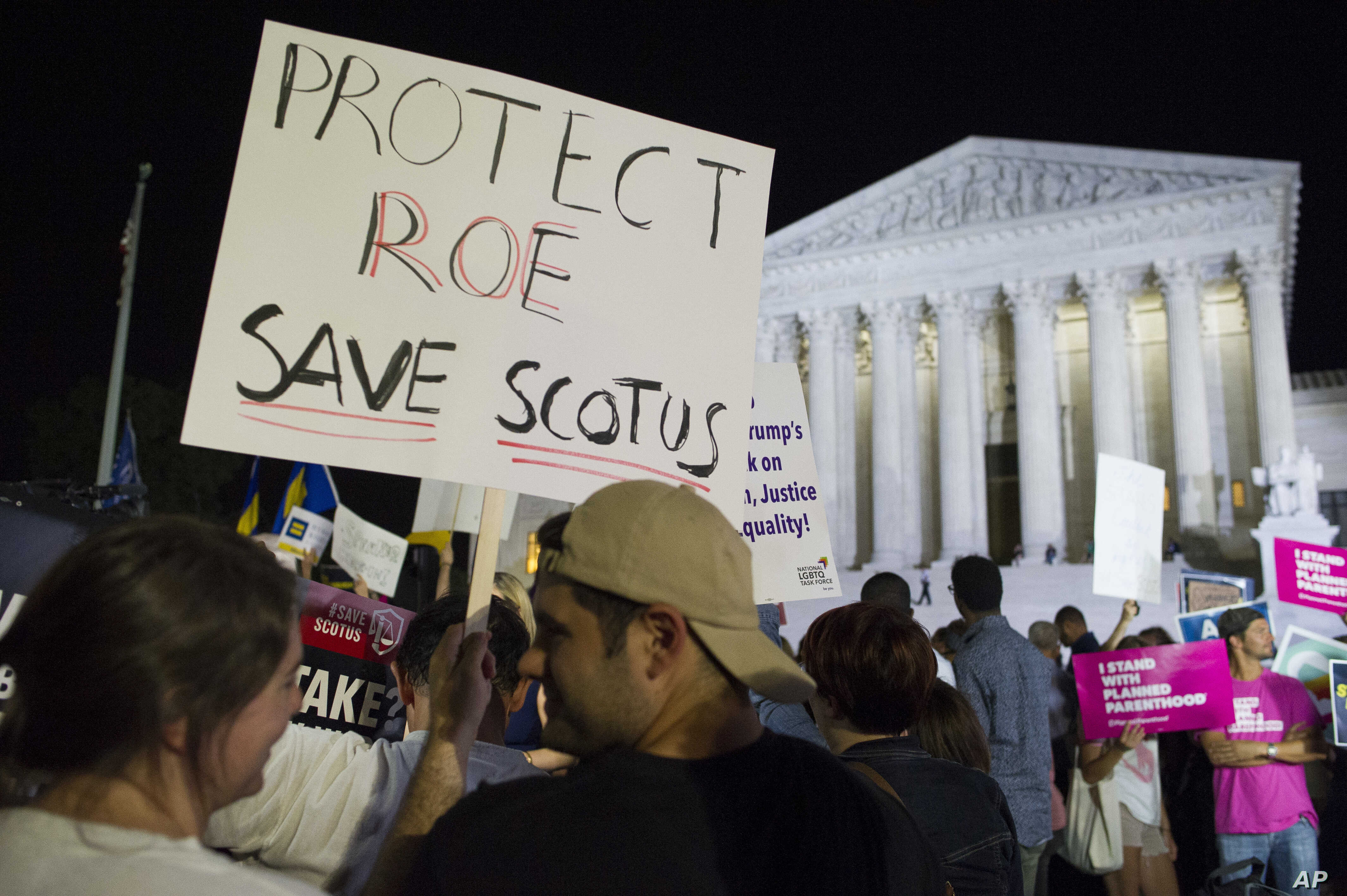 A demonstrator holds a sign as protesters gather in front of the Supreme Court in Washington, July 9, 2018, after President Donald Trump announced Judge Brett Kavanaugh as his Supreme Court nominee.