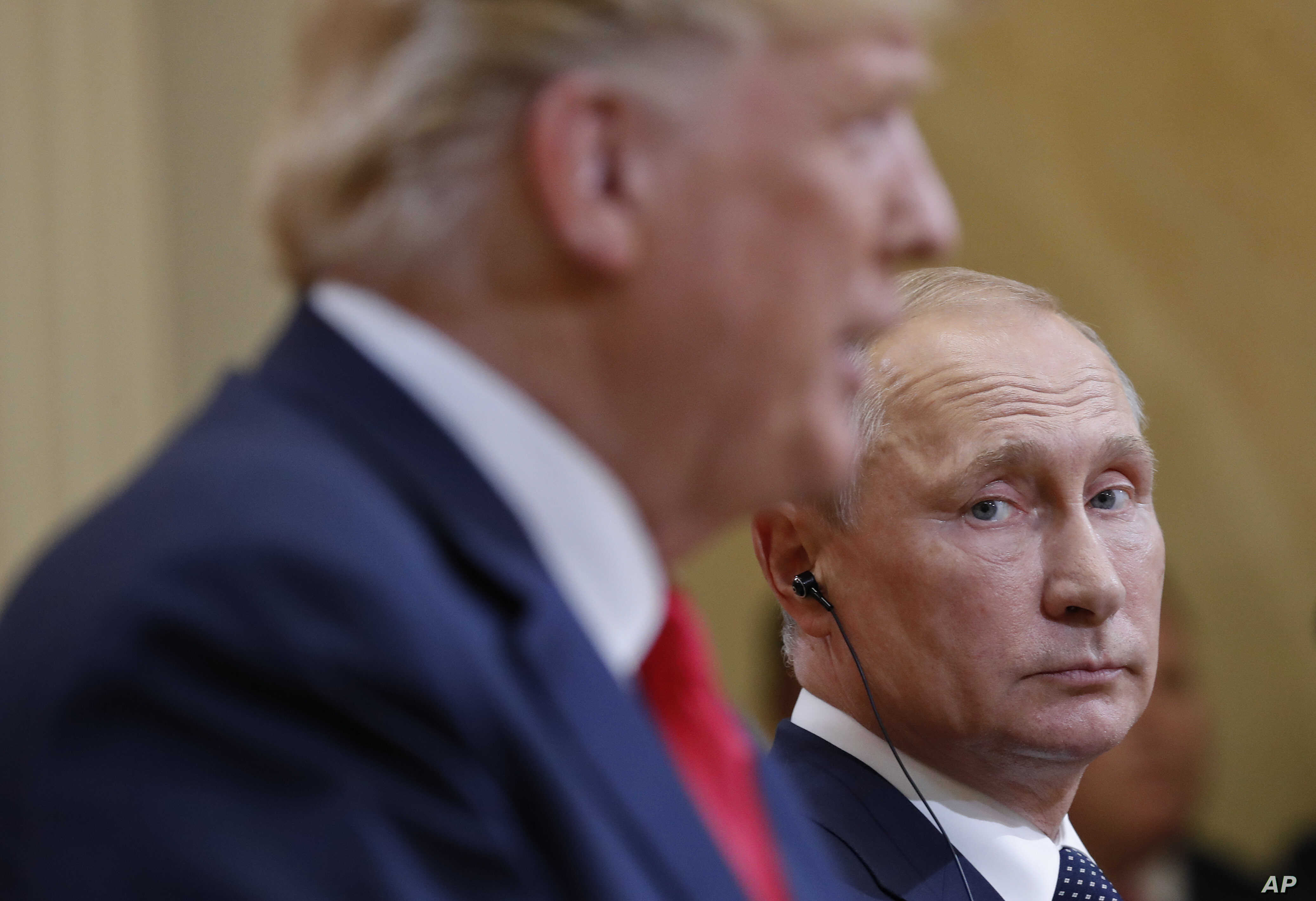 Russian President Vladimir Putin, right, looks over towards U.S. President Donald Trump, left, as Trump speaks during their joint news conference at the Presidential Palace in Helsinki, Finland, July 16, 2018.
