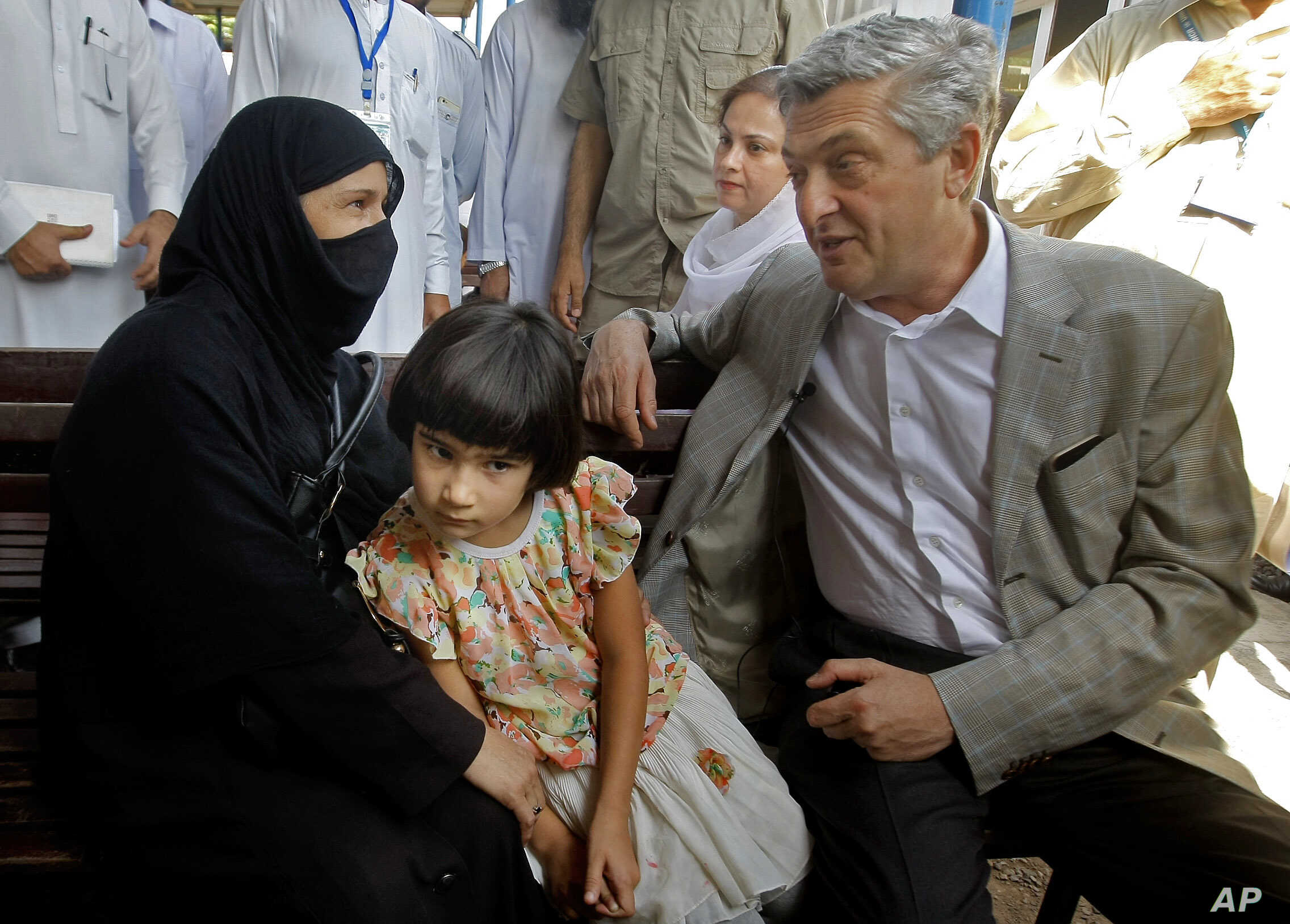 U.N. High Commissioner for Refugees Filippo Grandi talks to an Afghan refugee woman during his visit to the UNHCR's Repatriation Center in Peshawar, Pakistan, June 23, 2016.