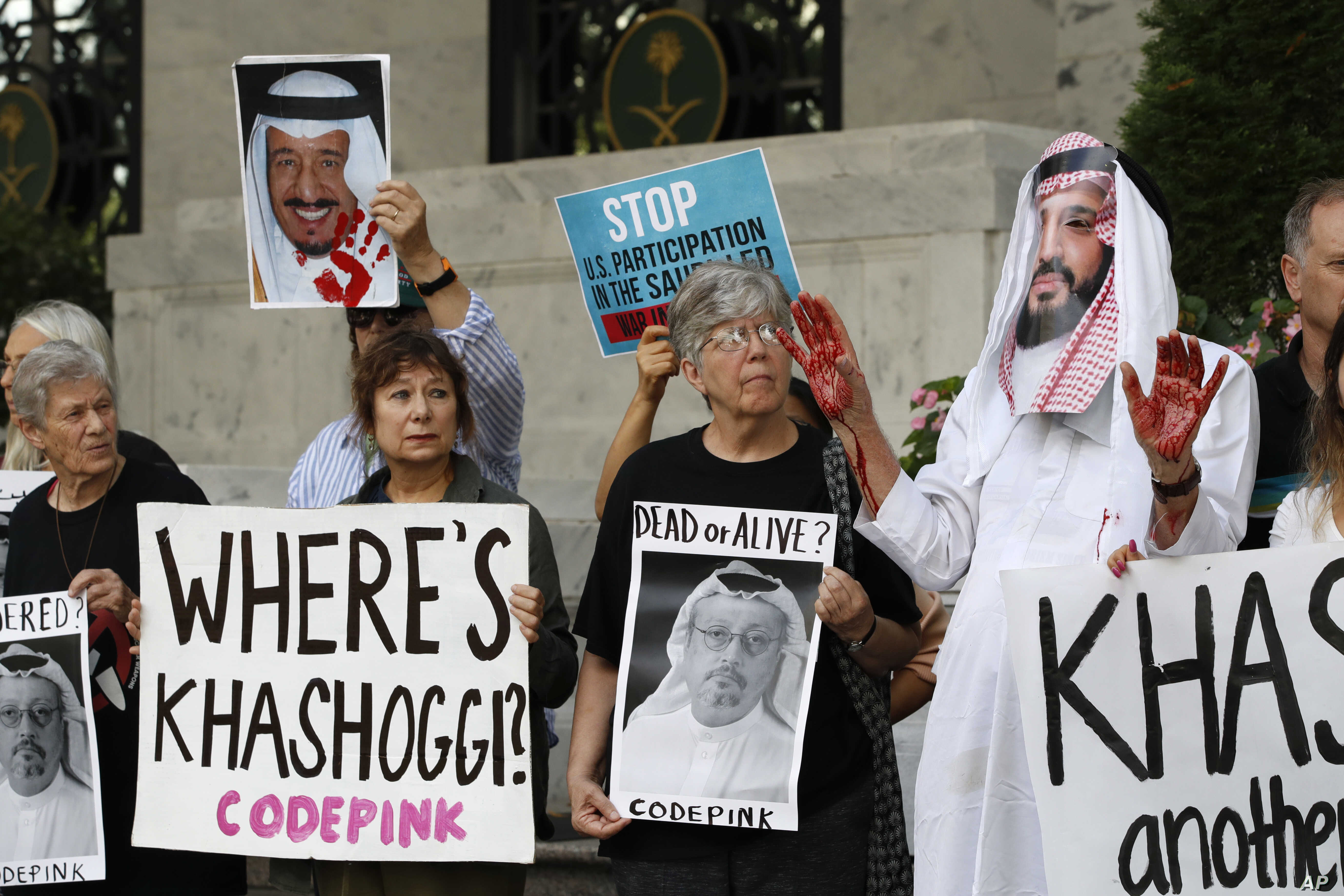 People hold signs at the Embassy of Saudi Arabia during a protest about the disappearance of Saudi journalist Jamal Khashoggi, Oct. 10, 2018, in Washington.