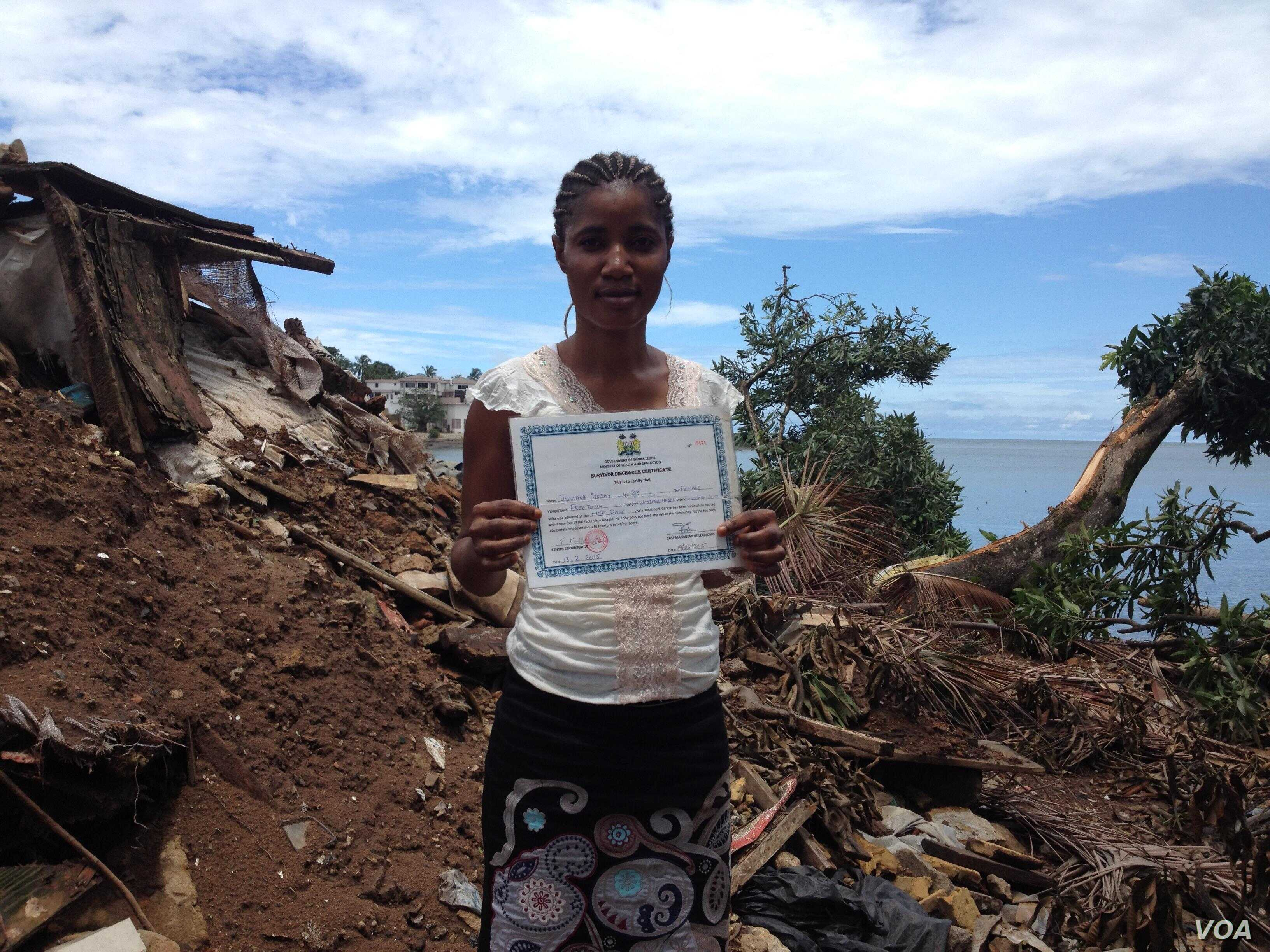 Ebola survivor Juliana Sesay stands where her house and business once stood, Freetown, Sierra Leone, Sept. 14, 2015. (VOA/N. Devries)