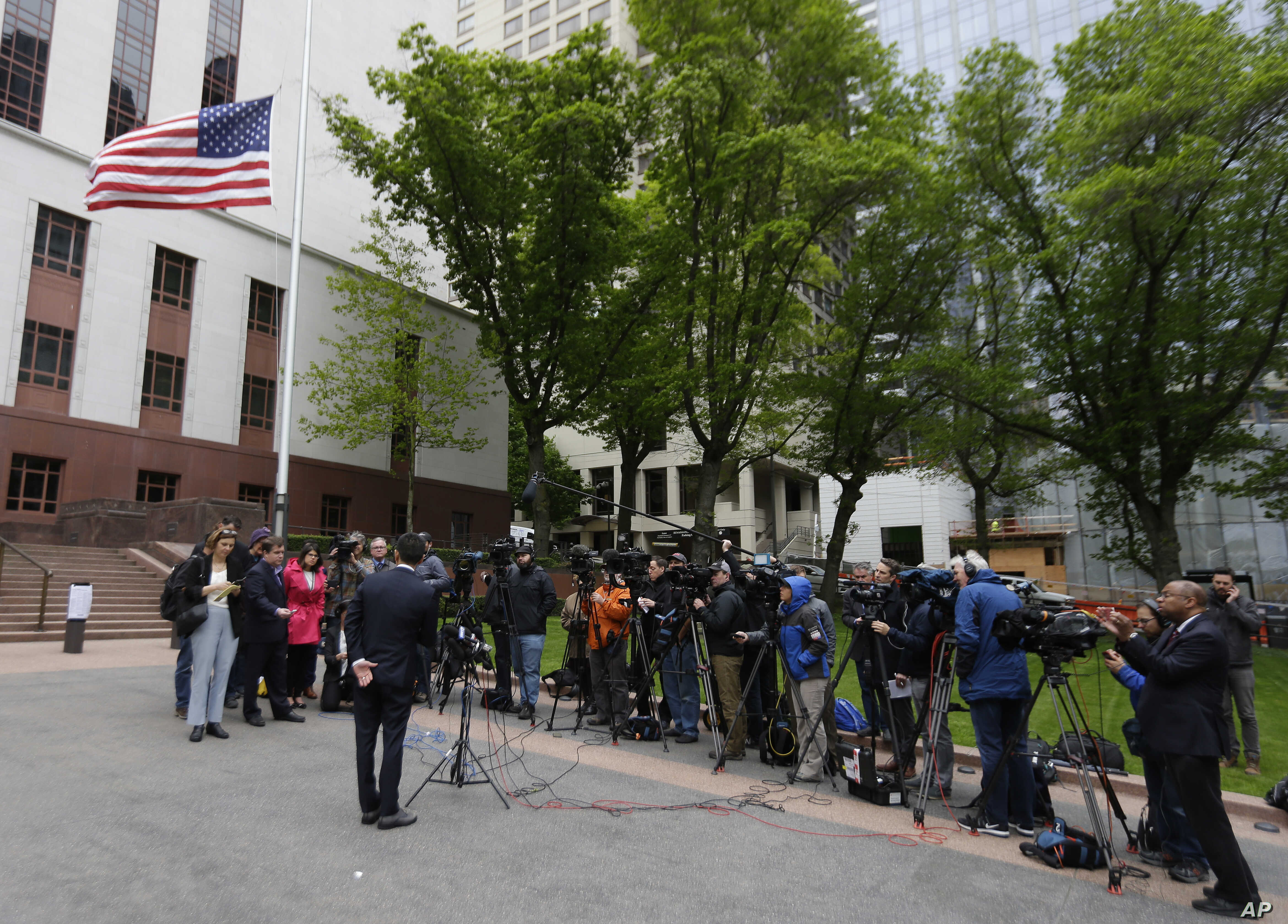Hawaii Attorney General Doug Chin (at left, with back to camera) talks to reporters outside a federal courthouse in Seattle, May 15, 2017. A three-judge panel of the 9th U.S. Circuit Court of Appeals heard arguments Monday in Seattle over Hawaii's la...