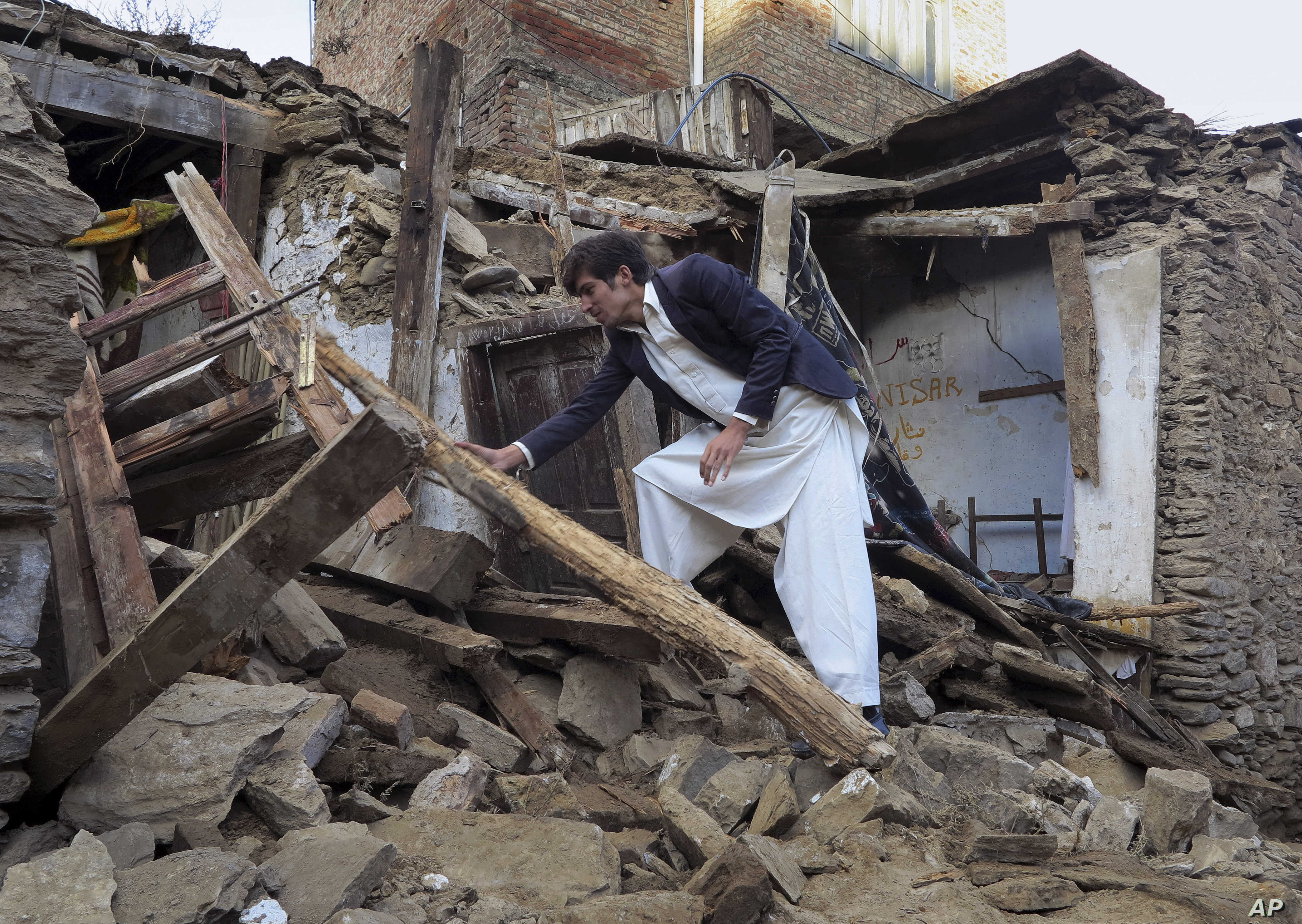 A Pakistani boy examines an earthquake-damaged house in Mingora, the main town of Swat valley, Oct. 27, 2015.
