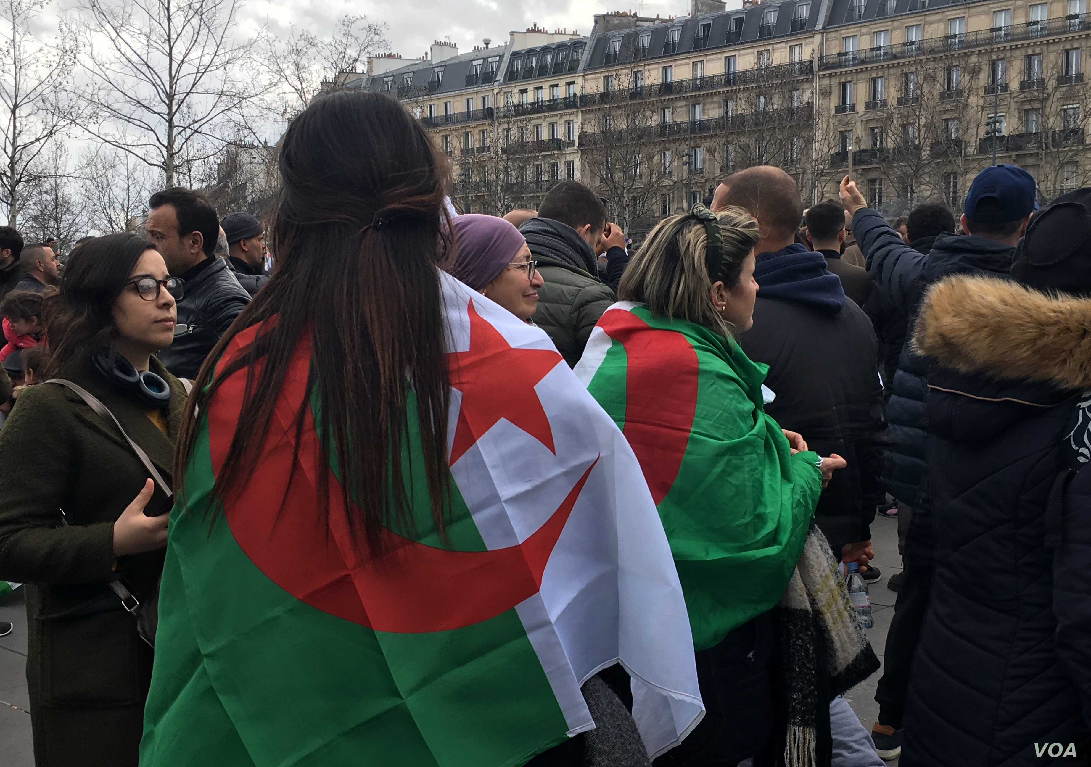 Women at a Paris protest are seen with the Algerian flag draped over their shoulders.