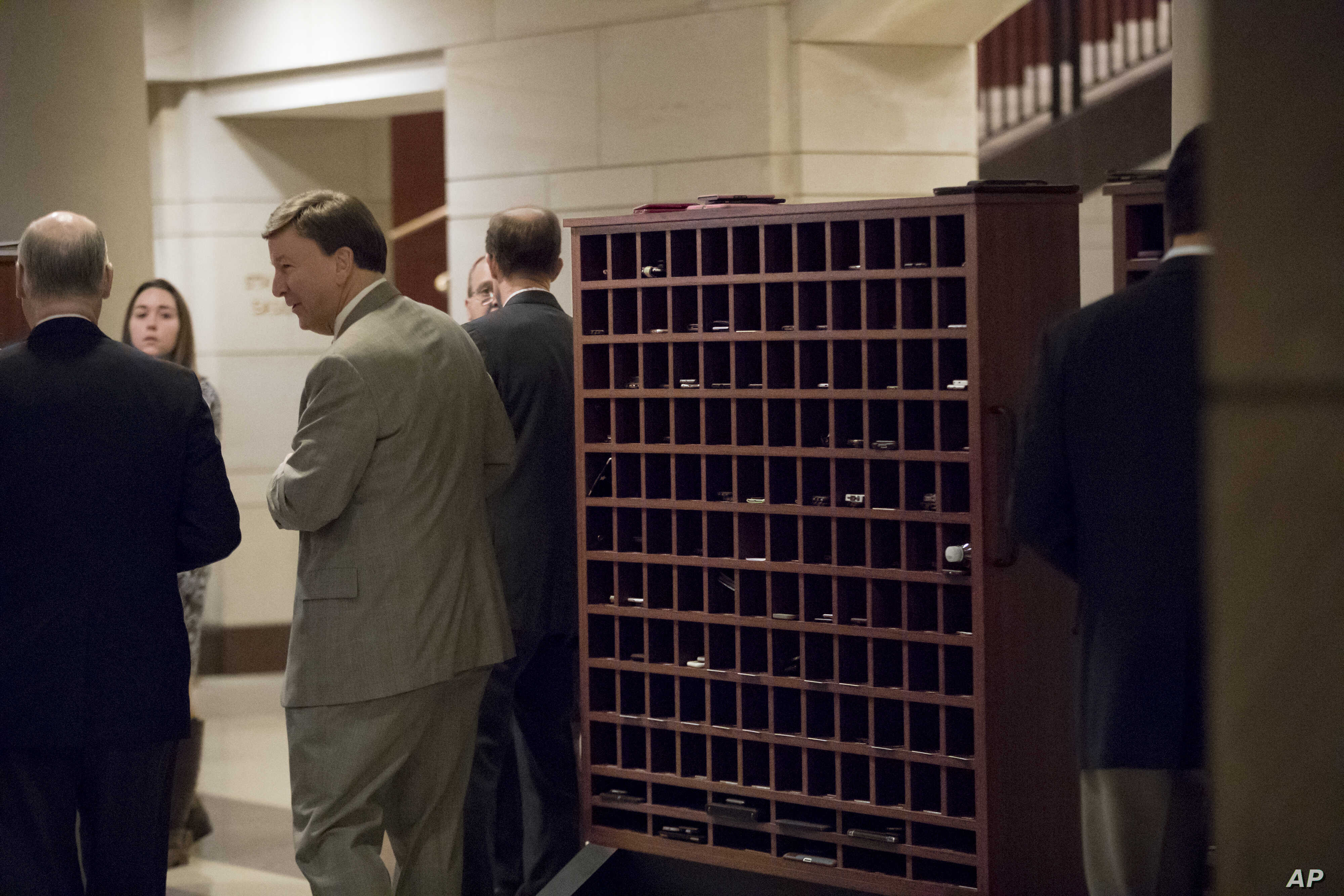 Members of Congress stow their cell phones and electronic devices before entering a closed-door intelligence briefing on Capitol Hill, Jan. 13, 2017.