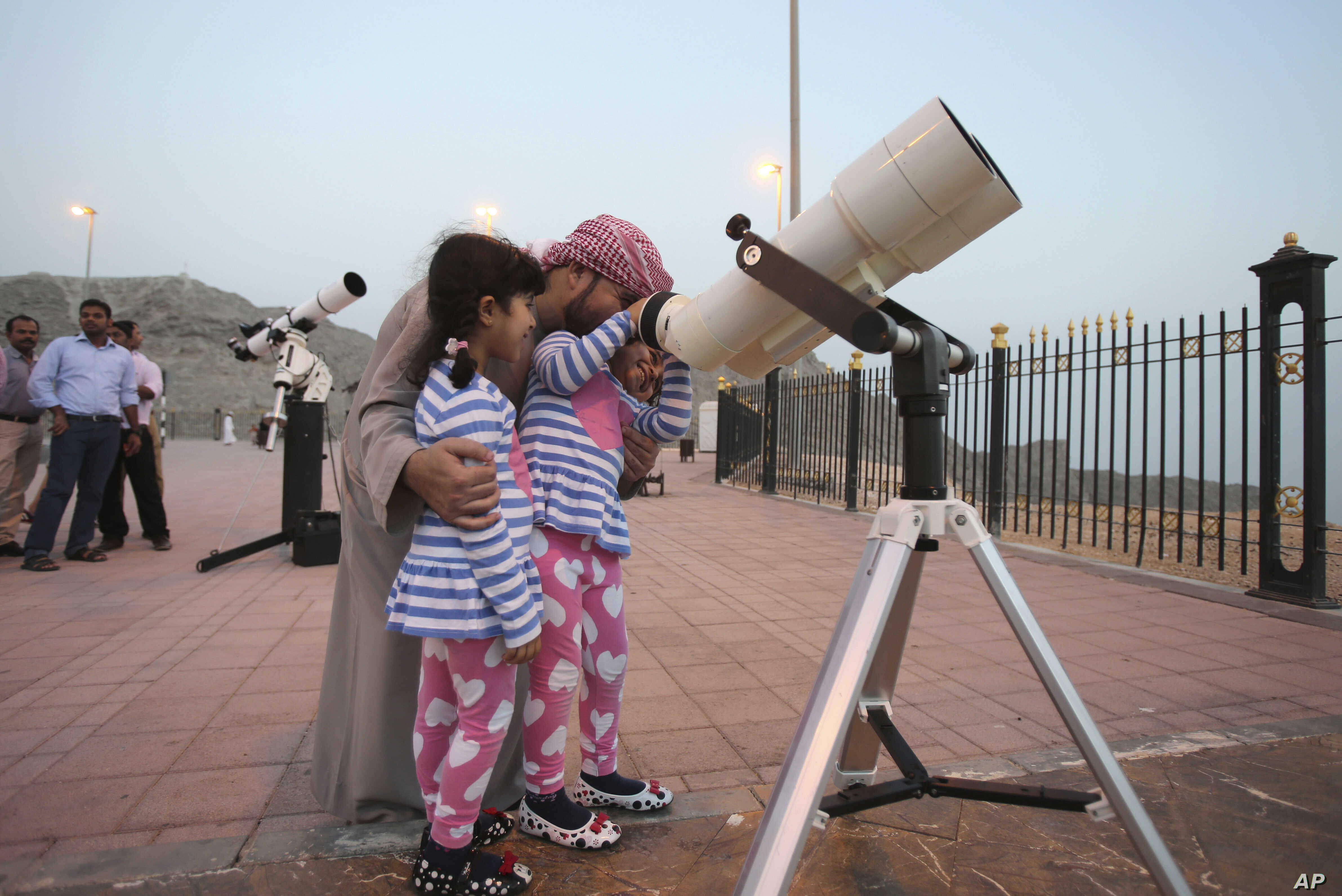 A father holds his girls as one of them looks into a telescope during a moon sighting event on top of Jebel Hafeet mountain ahead of the holy month of Ramadan, in Al Ain, United Arab Emirates, June 16, 2015.