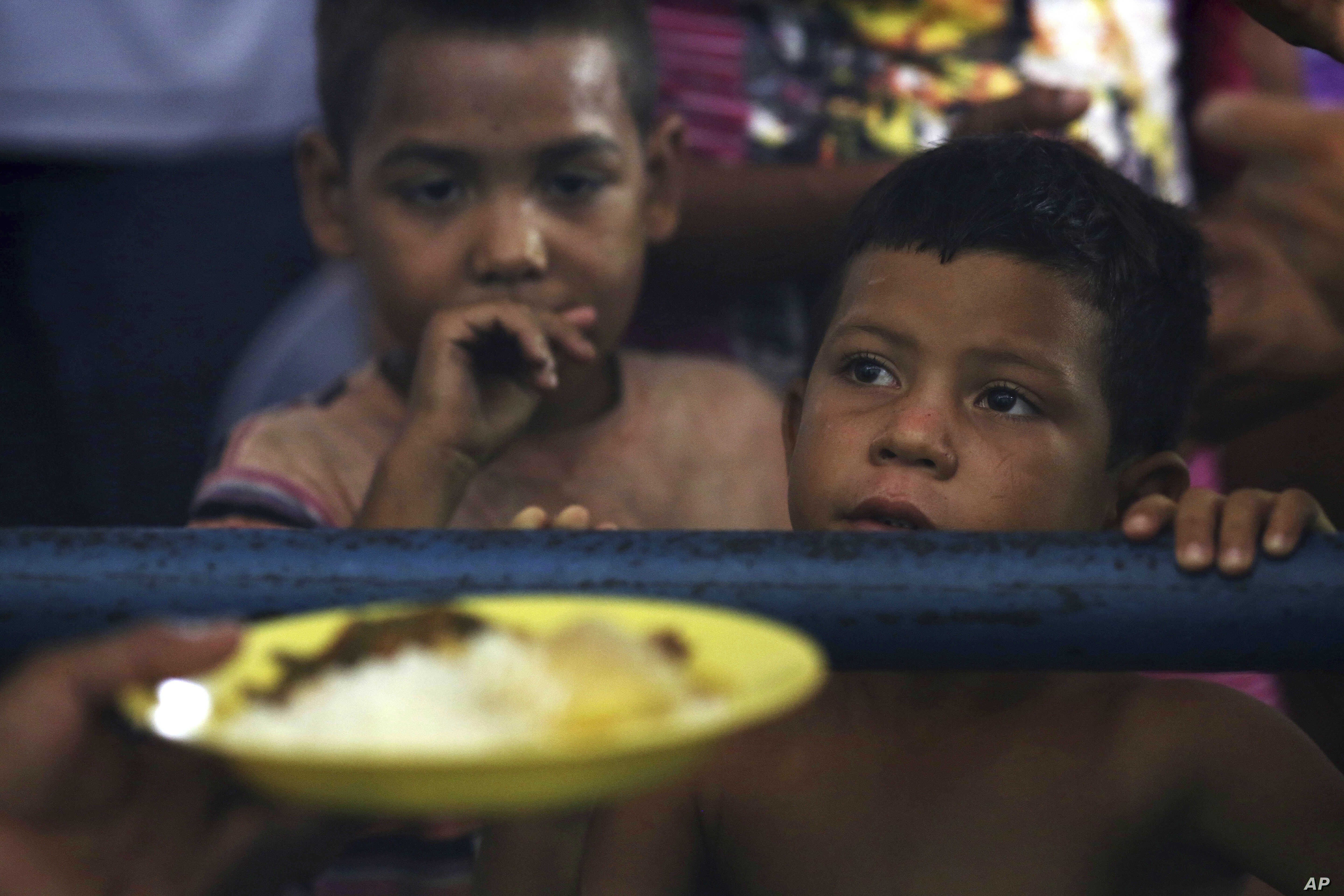In this March 8, 2018 photo, Venezuelan children wait for a free meal at a migrant shelter set up at the Tancredo Neves Gymnasium in Boa Vista, Roraima state, Brazil.