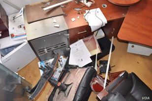 Ahmed shows this picture on his cellphone of his former office, smashed by men hunting him for revenge in a lawless part of Libya, July 8, 2016. (Photo: H. Murdock / VOA)