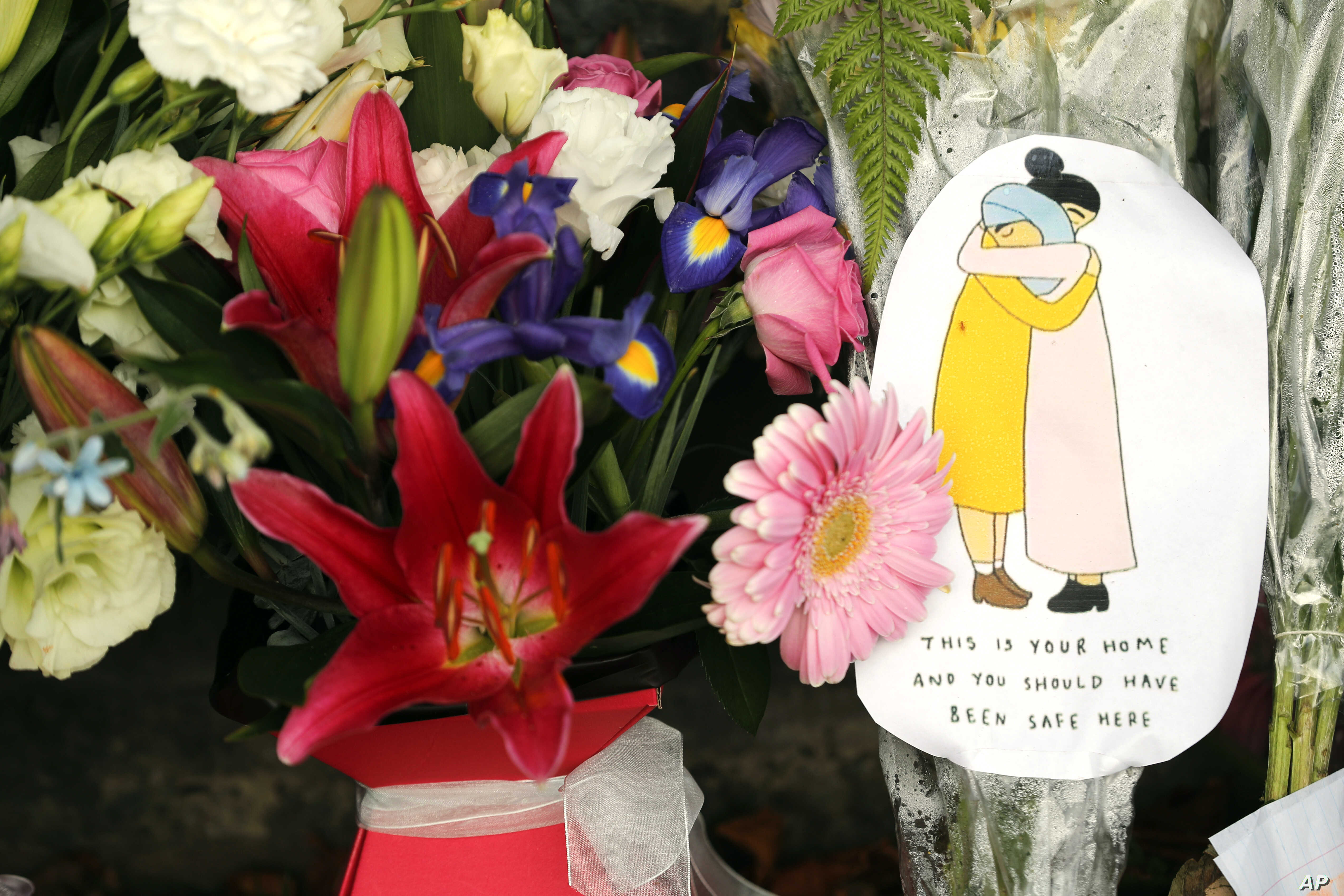 A message card is placed at a collection of flowers left at the Botanical Gardens in Christchurch, New Zealand, March 16, 2019.