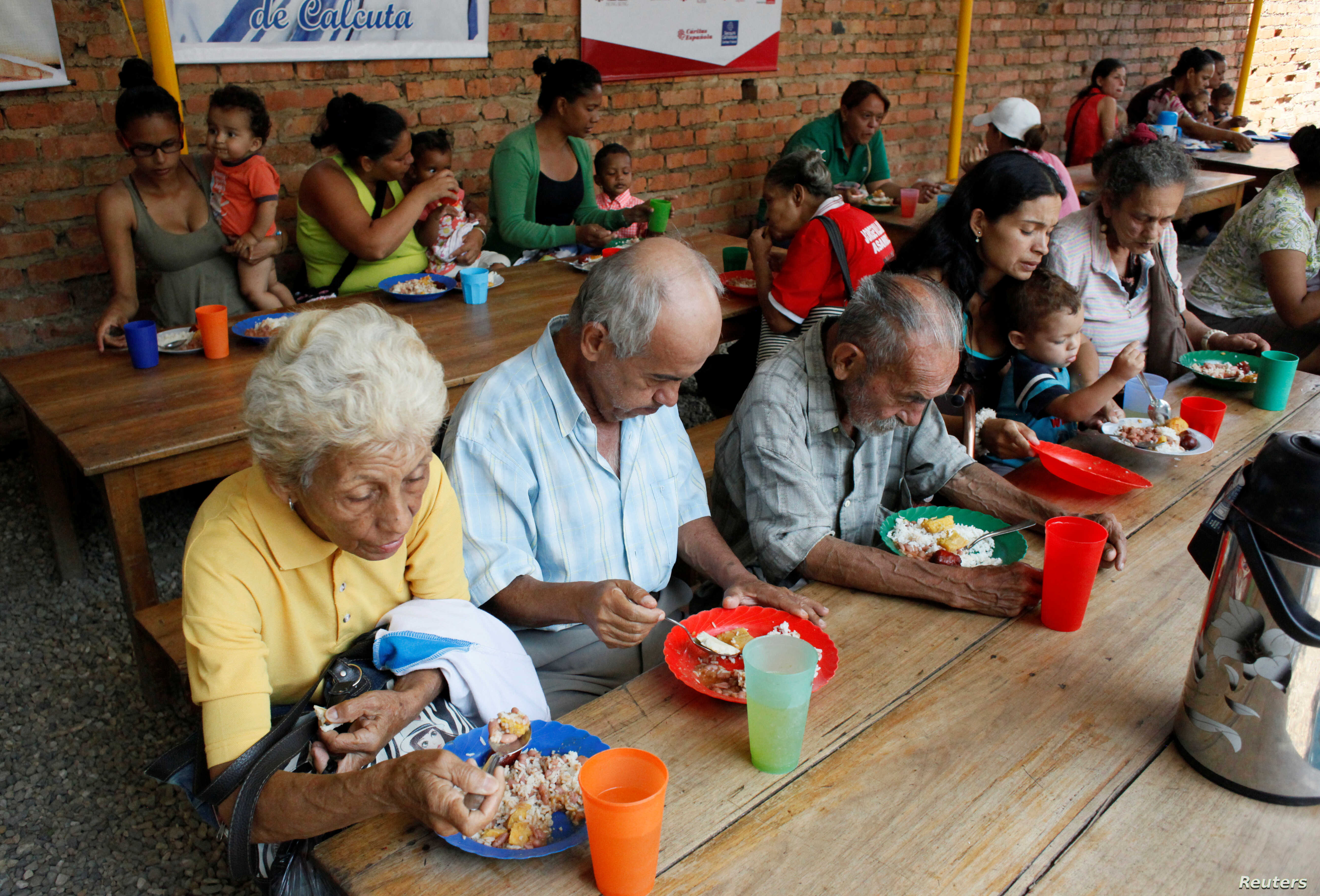 Venezuelans have a meal at a dining facility organized by the Catholic church, in Cucuta, Colombia, Feb. 21, 2018.