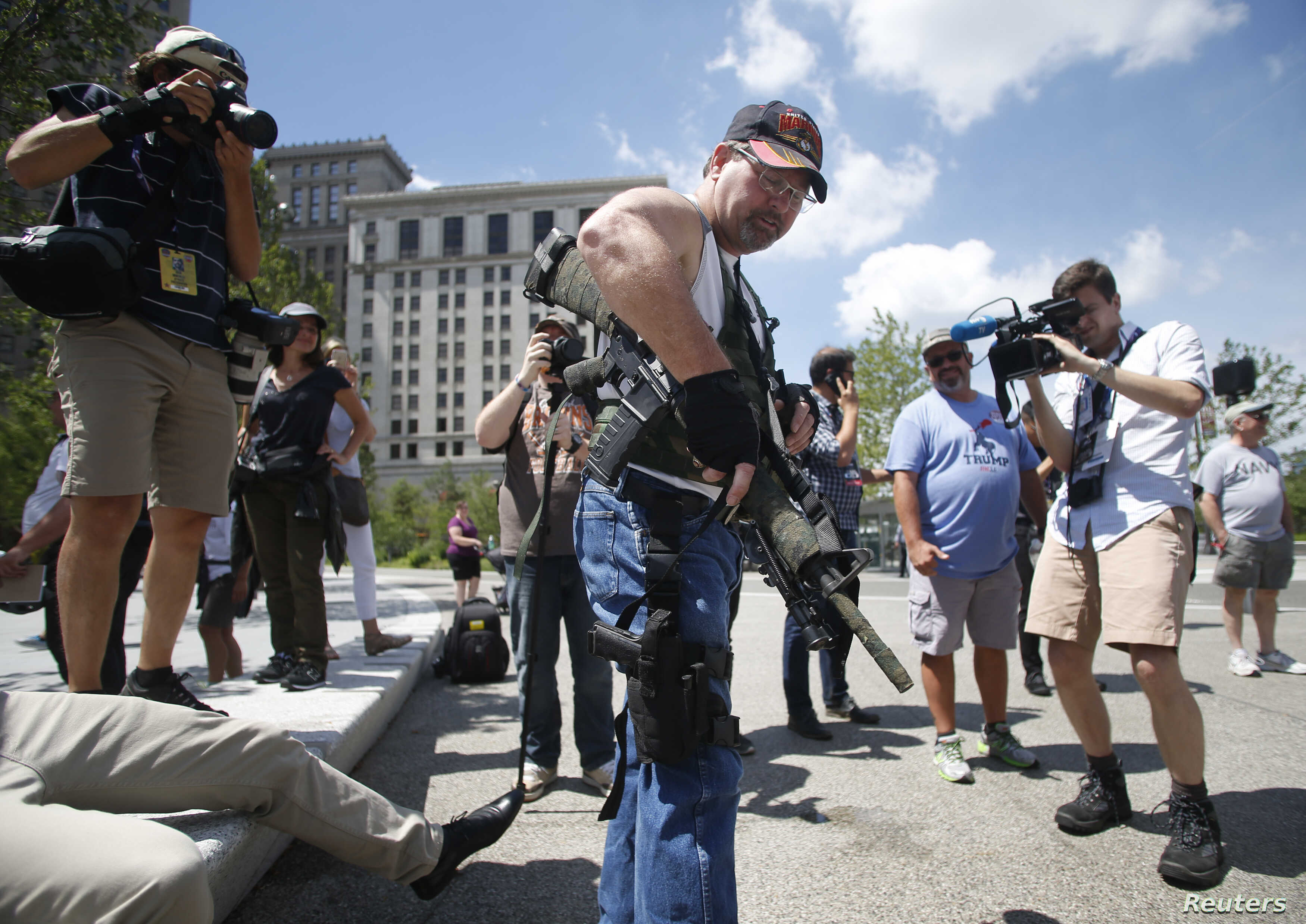 Steve Thacker carrying a rifle and a handgun is surrounded by news media in a public square in Cleveland, Ohio, July 17, 2016.
