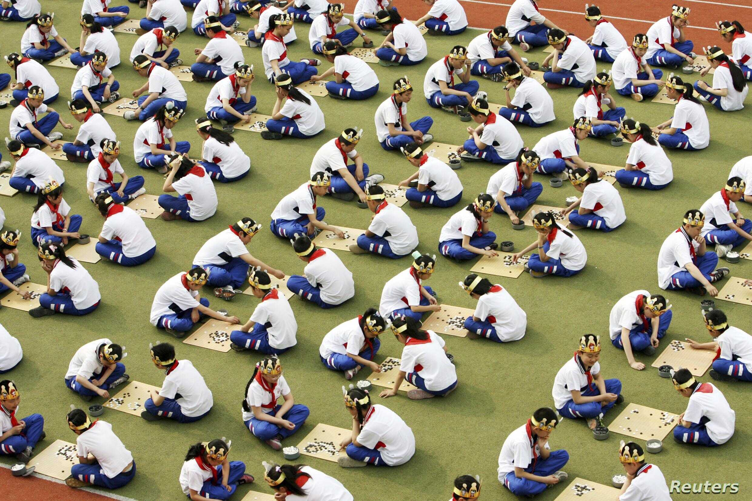 """FILE - Students play the board game """"Go,"""" known as """"Weiqi"""" in Chinese, during a competition to mark the 100-day countdown to the opening of Beijing Olympics at a primary school in Suzhou, Jiangsu province, April 30, 2008."""