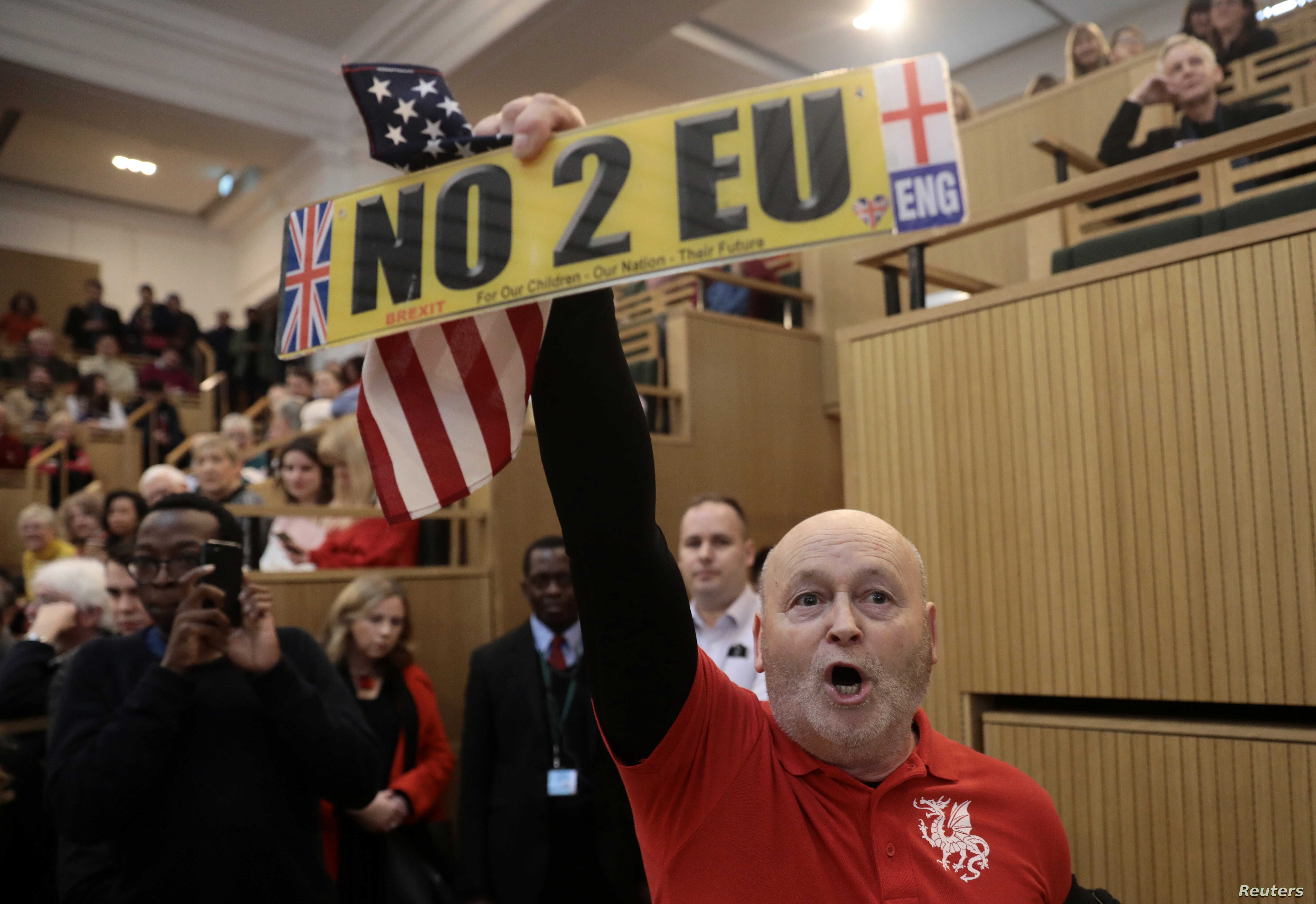A demonstrator holds a pro-Brexit sign and a U.S. flag, as the speech by the Mayor of London, Sadiq Khan, is interrupted at the Fabian Society New Year Conference, in central London, Britain Jan. 13, 2018.