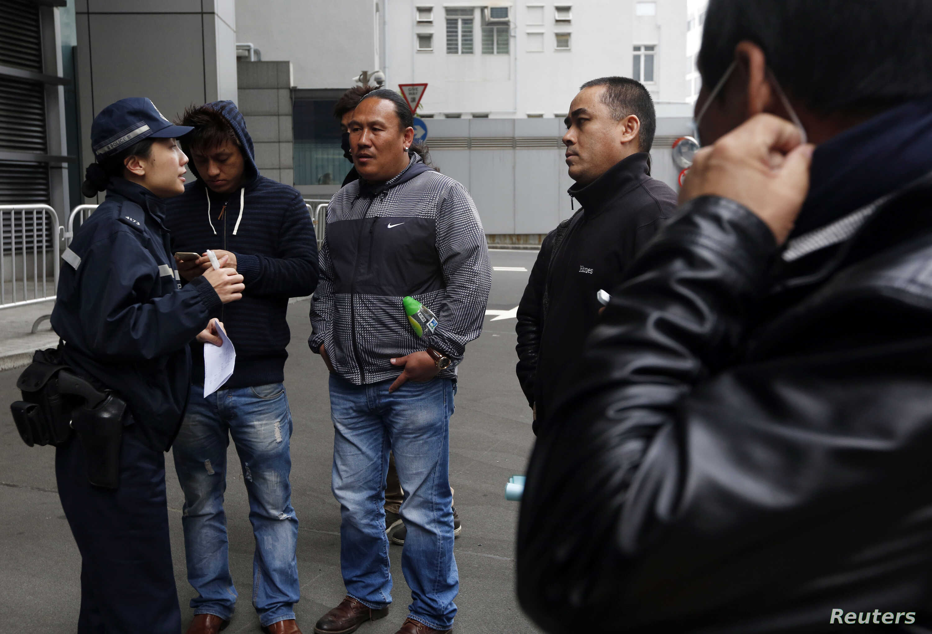 FILE - A policewoman talks to a group of Nepalese men, who have invested in bitcoin, outside the police headquarters in Hong Kong Feb. 11, 2015. Hong Kong lawmakers at that time urged authorities to ban bitcoin as more than 25 people flocked to polic...