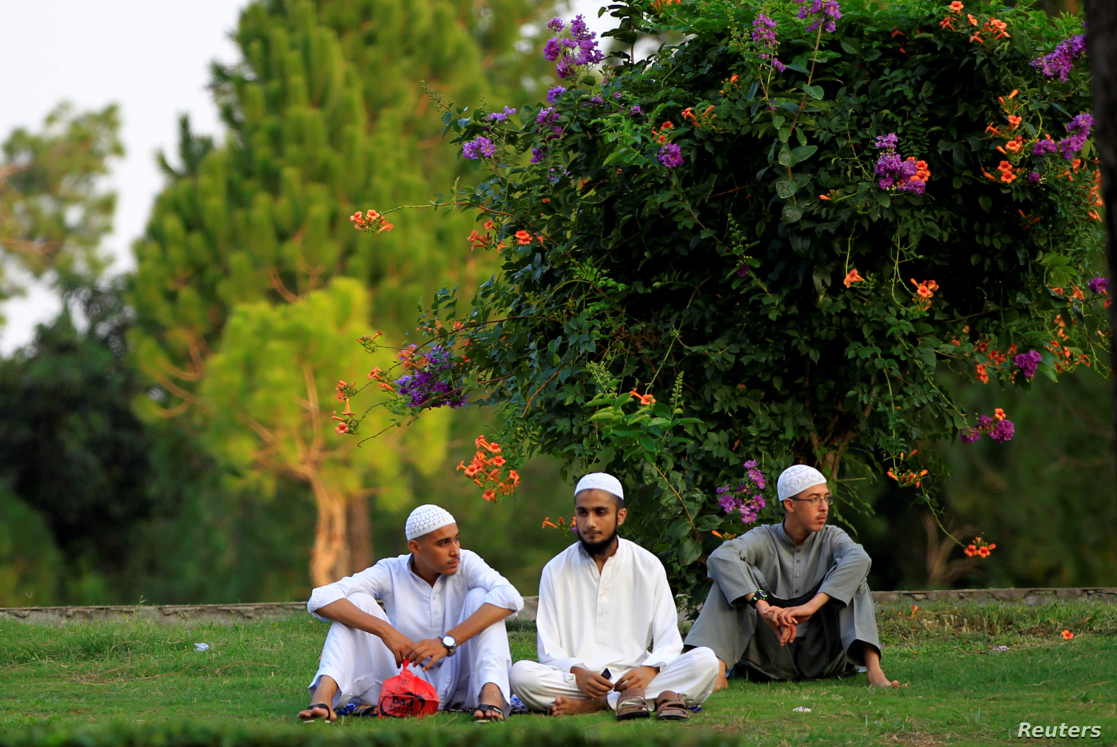 Students from a local madrassa rest on the lawn near a traffic light in Islamabad, Pakistan July 14, 2017.