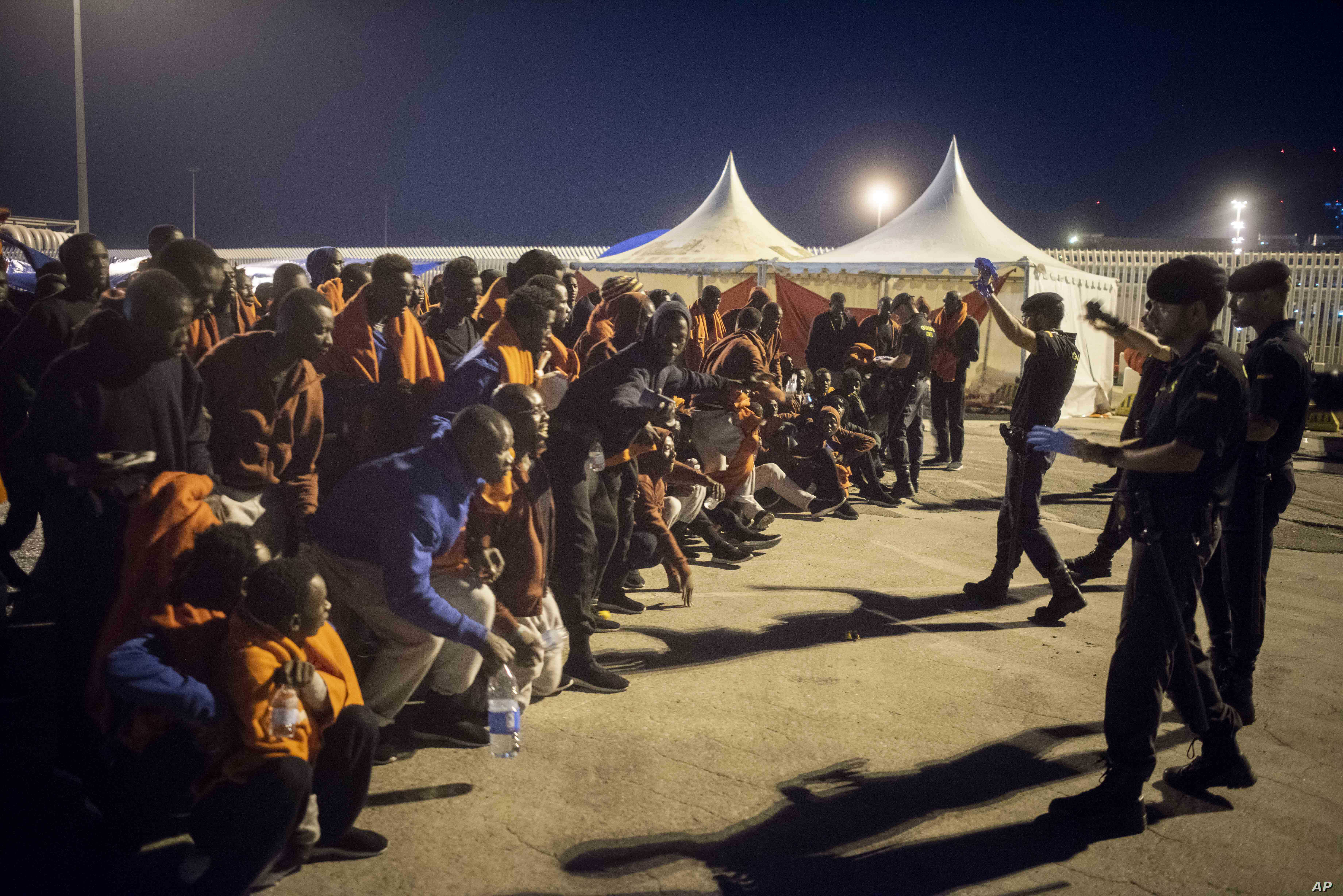 A group of migrants react in front of Spanish Police officers at the port of Algeciras, southern Spain, after being rescued by Spain's Maritime Rescue Service in the Strait of Gibraltar, July 31, 2018. Spain's foreign minister says the European Union...