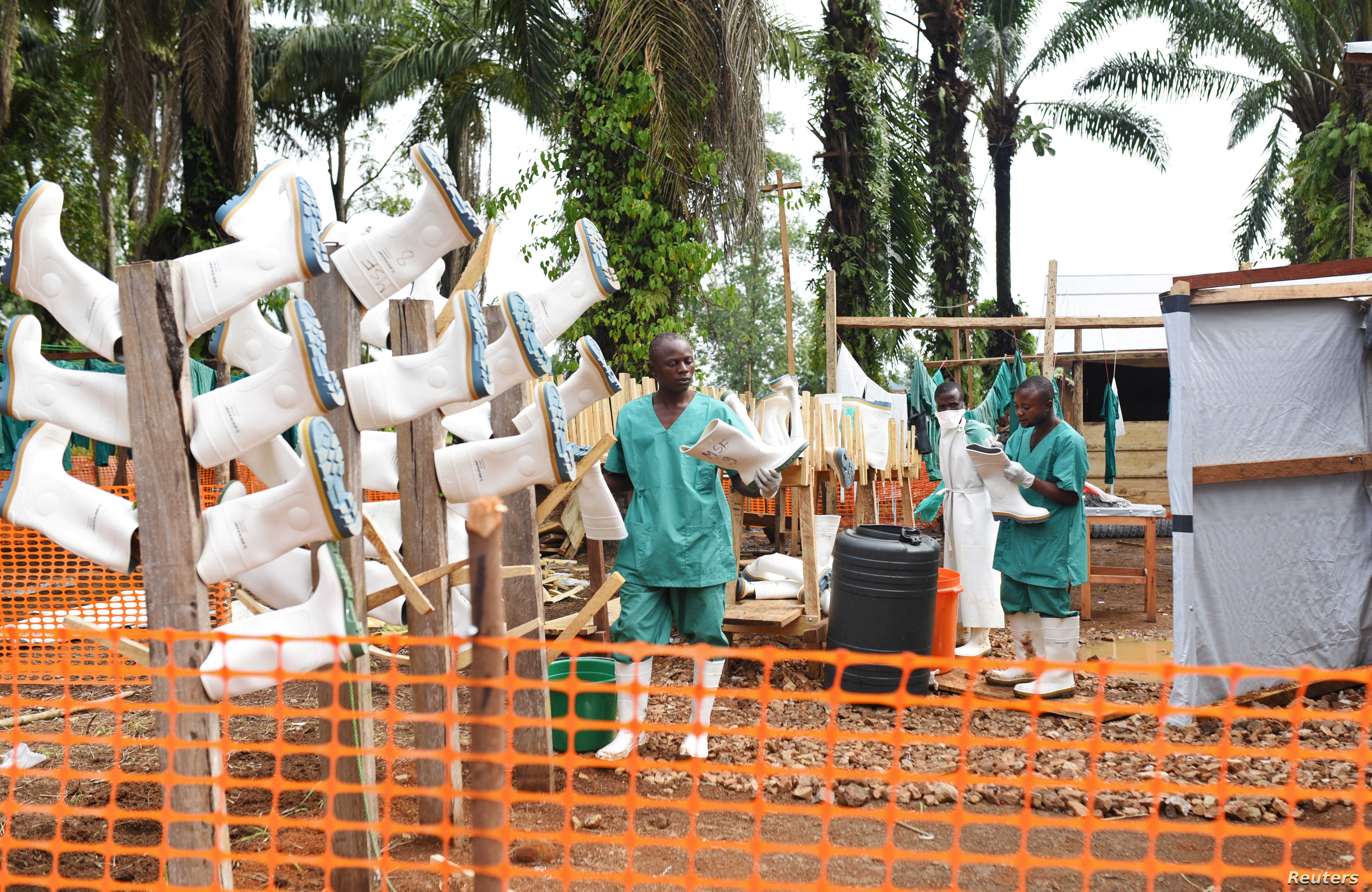 Congolese health workers clean gumboots as they prepare the Ebola treatment center in the village of Mangina in North Kivu province of the Democratic Republic of Congo, Aug. 18, 2018.