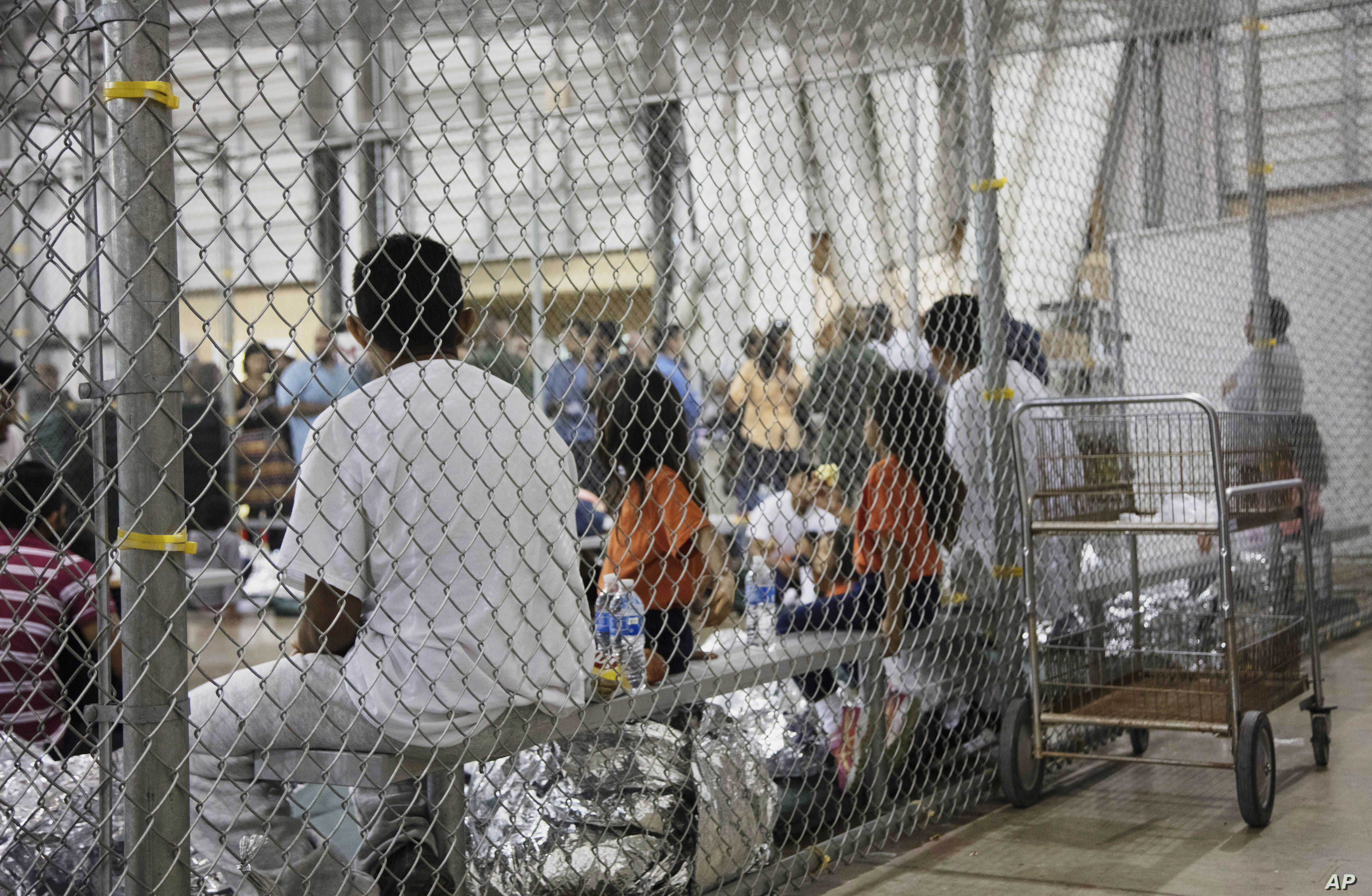 FILE - People who've been taken into custody related to cases of illegal entry into the United States, sit in one of the cages at a facility in McAllen, Texas, June 17, 2018. Records obtained by The Associated Press highlight some of the problems tha...