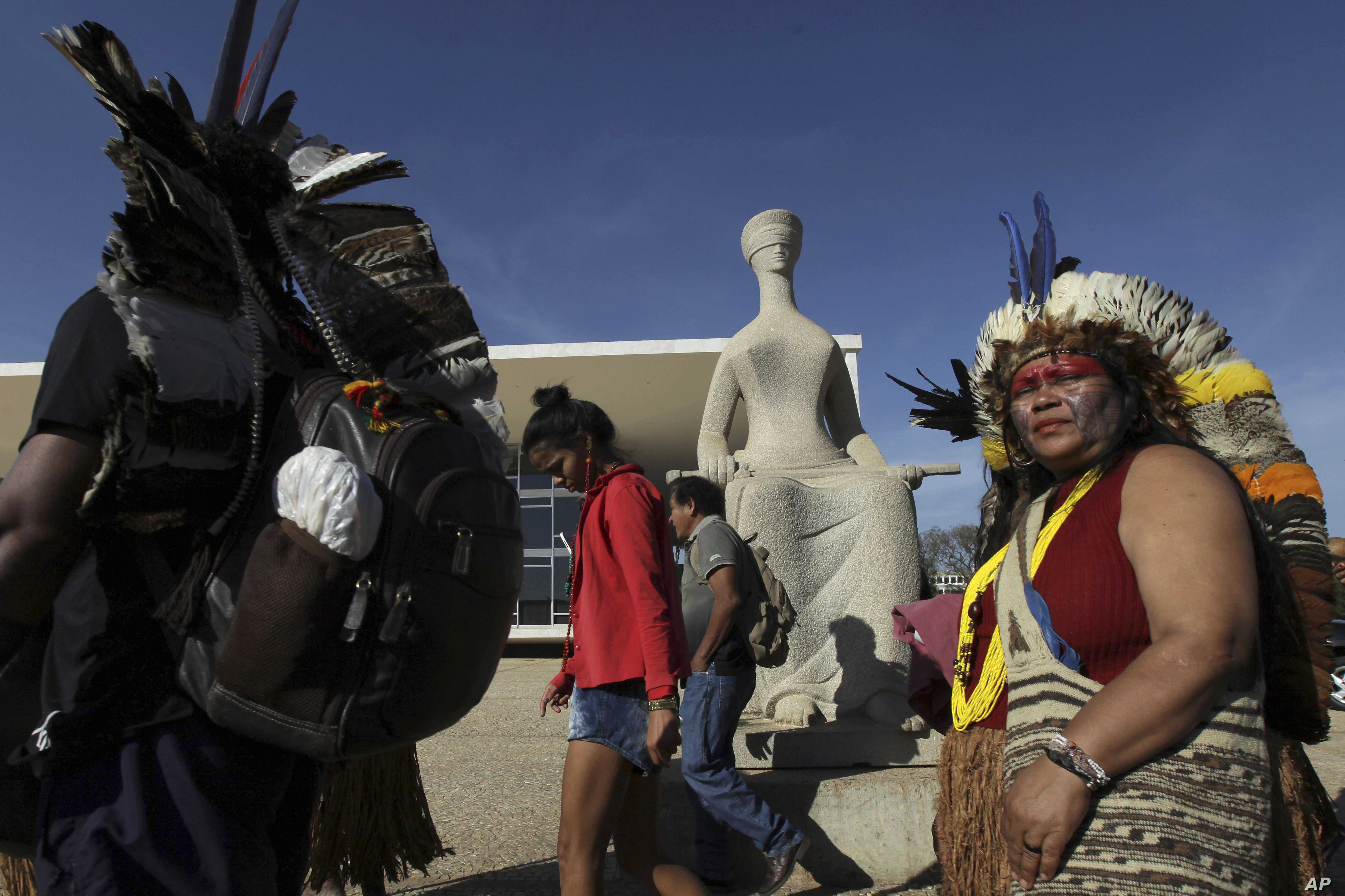 Indians walk past a statue of justice as they protest outside the Supreme Court, in Brasilia, Brazil, Aug. 16, 2017. Brazil's indigenous communities protested as the Supreme Court deliberated on the legality of President Michel Temer's plan to restri...