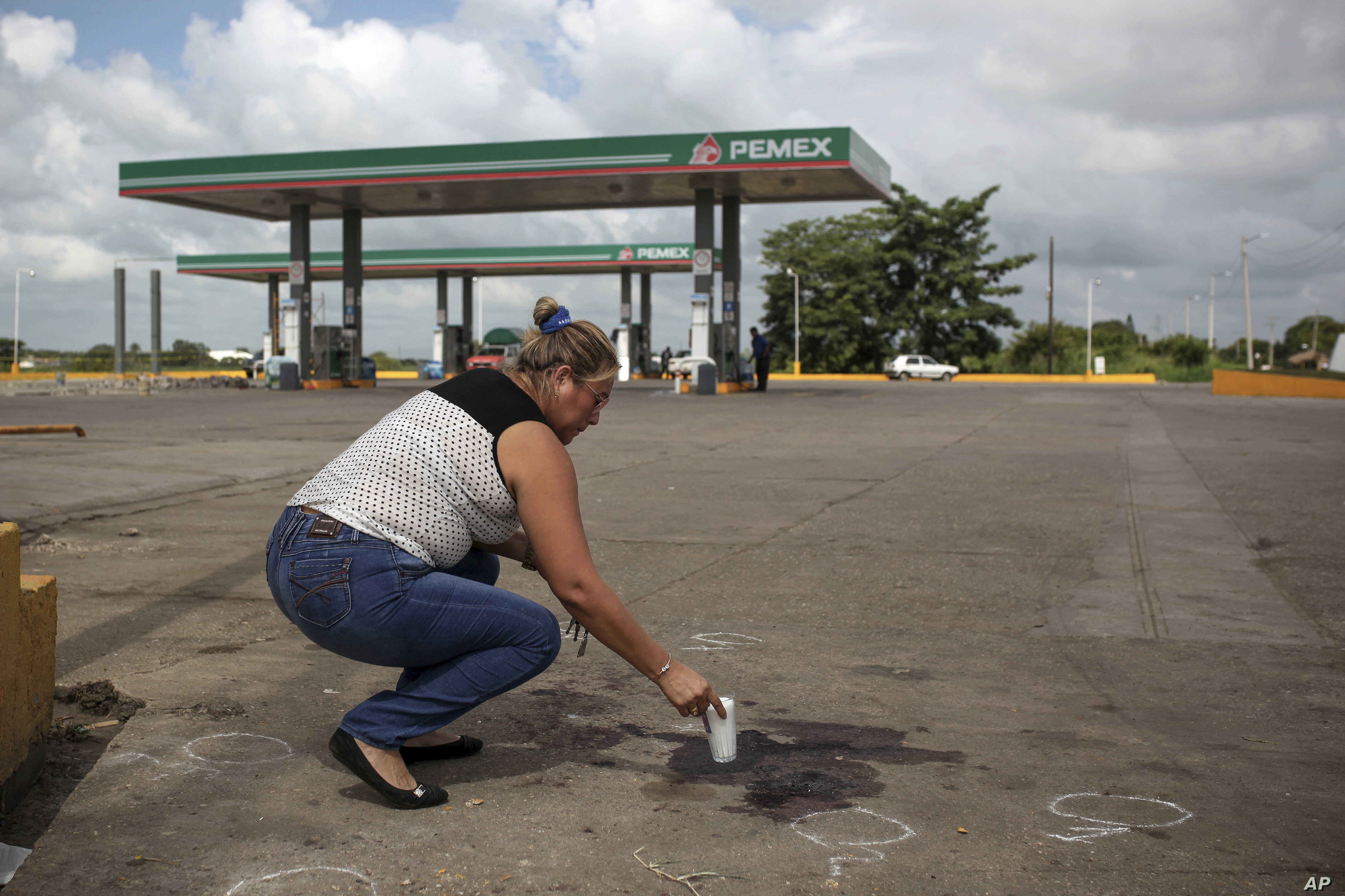 A woman places a candle at the gas station where Candido Rios Vazquez, a reporter for the Diario de Acayucan, was murdered in Hueyapan de Ocampo, Veracruz state, Mexico, Aug. 23, 2017. The National Human Rights Commission said that Rios was the ninth...