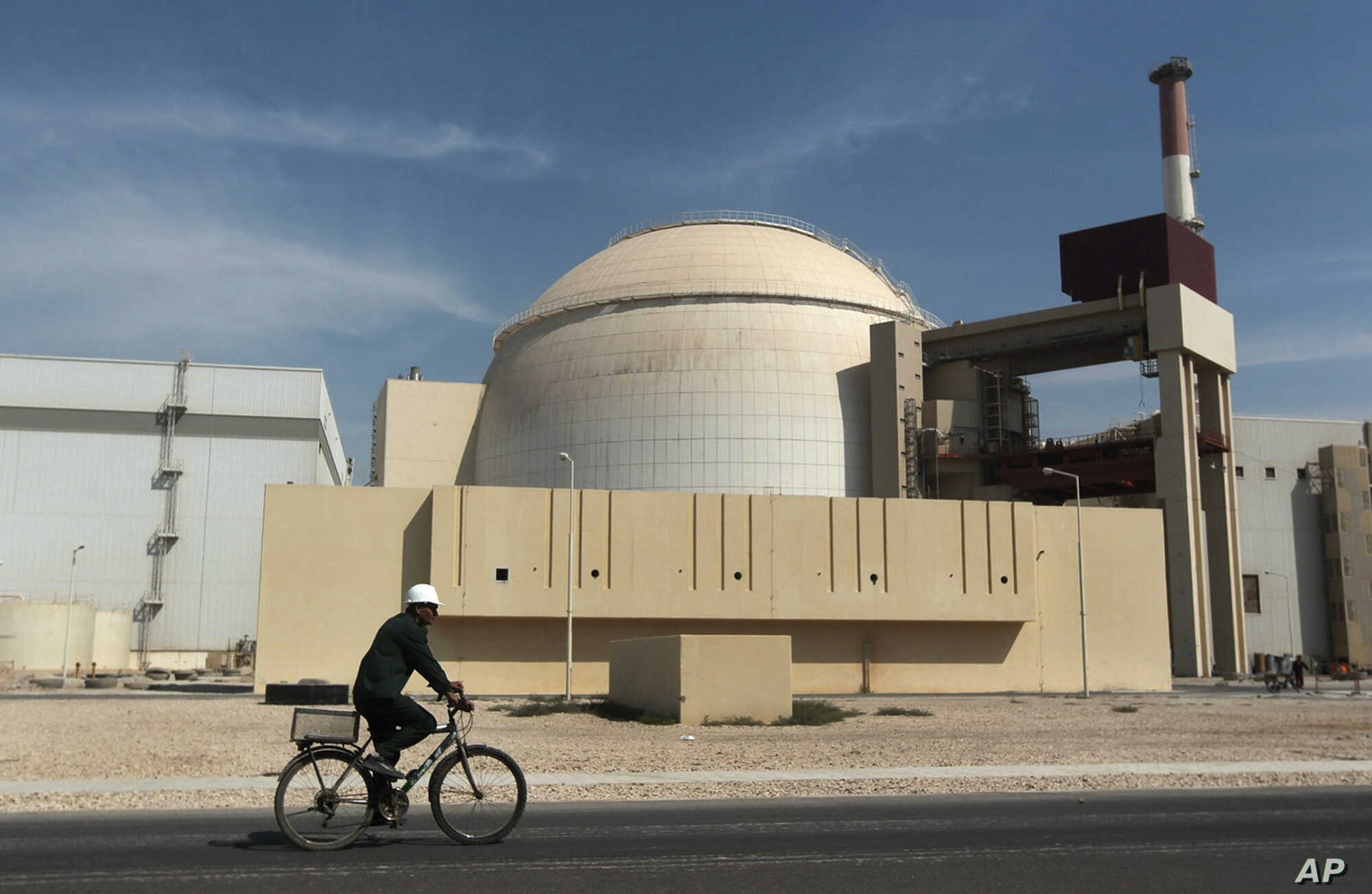 FILE: A bicyclist passes the nuclear power plant just outside Bushehr, Iran, on Oct. 26, 2010. U.S. and Iranian representatives plan to meet before the next round of nuclear talks with world powers.