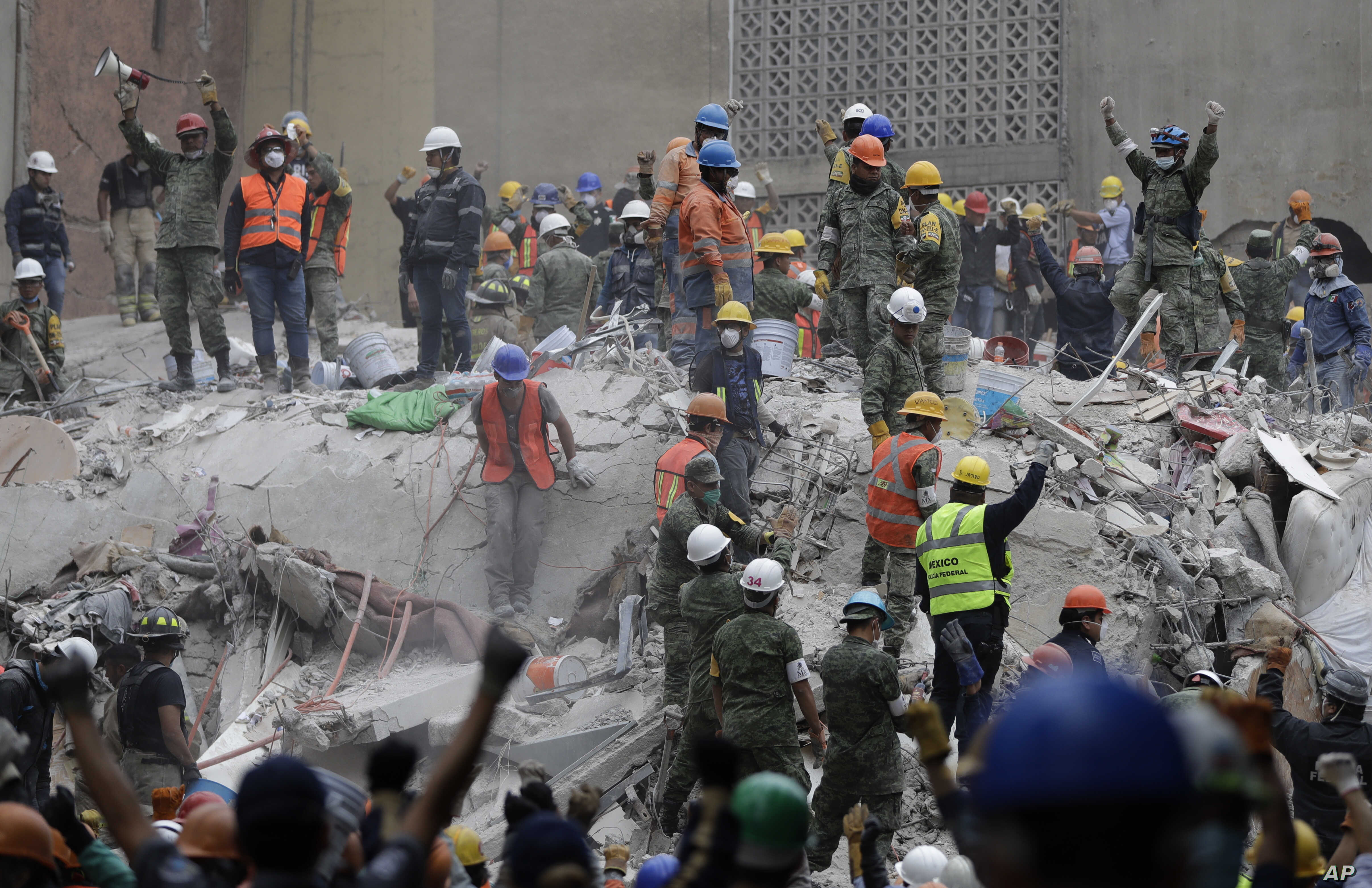 Rescue workers, some holding their arms up as a sign to maintain silence,  search for survivors at an apartment building at Amsterdam and Laredo streets that collapsed during an earthquake in the Condesa neighborhood of Mexico City, Mexico, Sept. 21,