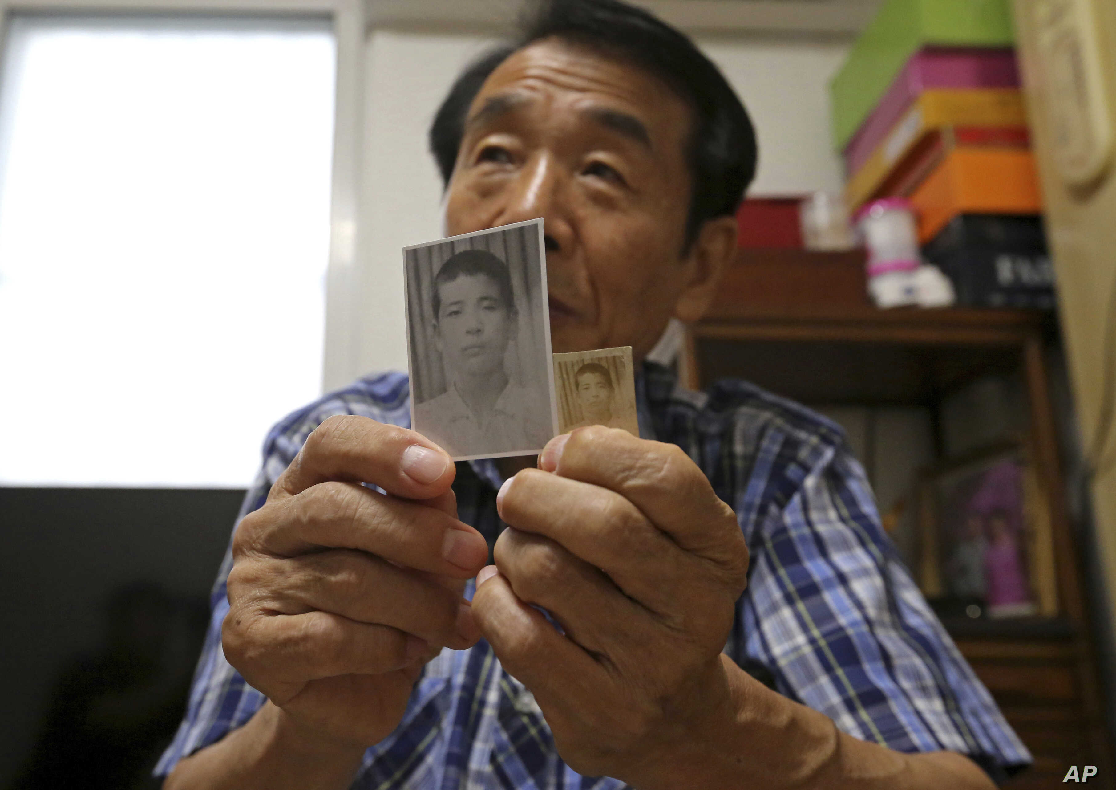 Lee Soo-nam, 76, shows photos of his brother Ri Jong Song in North Korea during an interview at his home in Seoul, South Korea, Aug. 17, 2018. Starting Monday, Lee will join about 200 war-separated South Koreans and their family members who are cross...