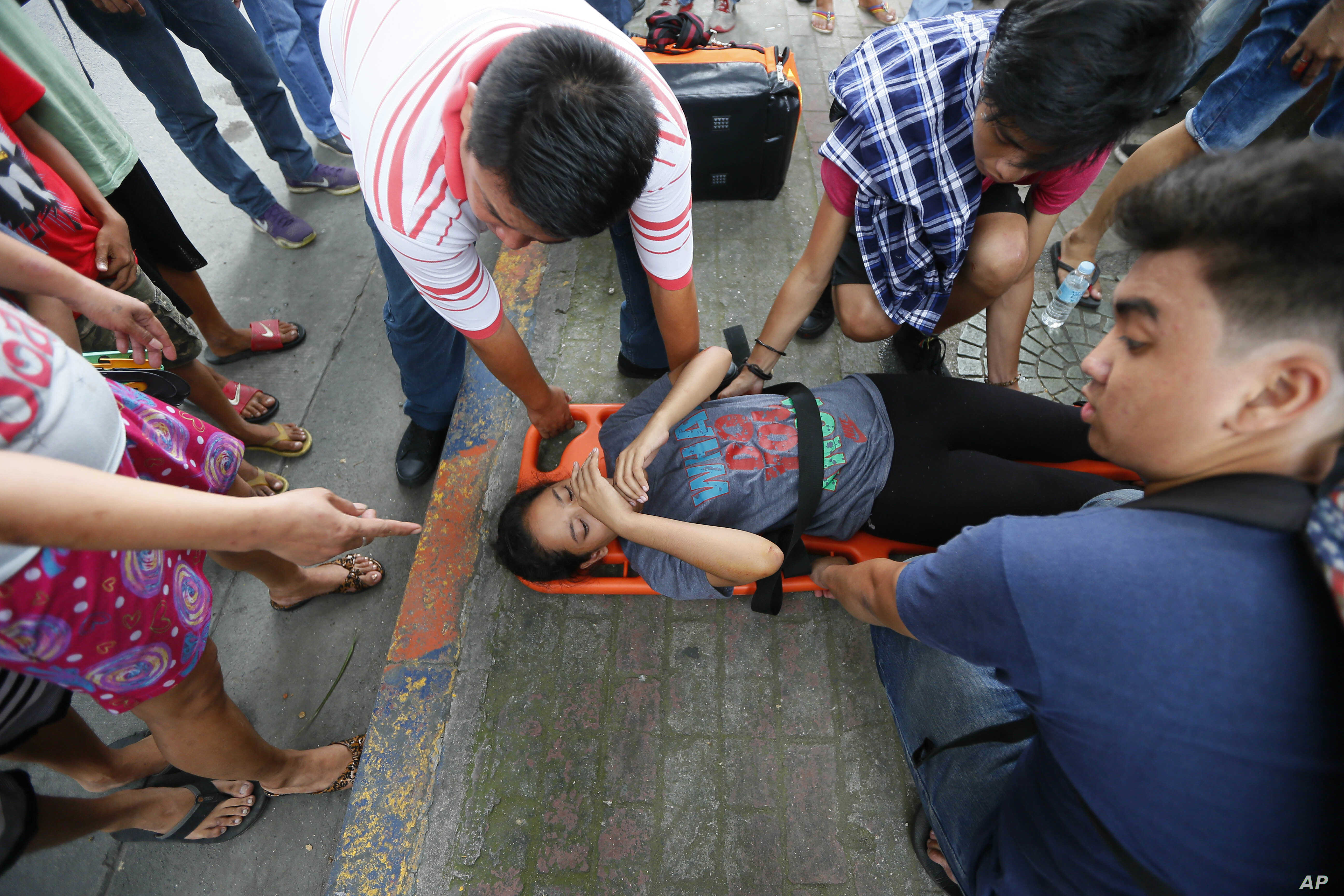 A protester who was run over by a Philippine National Police van waits for treatment outside the U.S. Embassy in Manila, Philippines, Oct. 19, 2016.