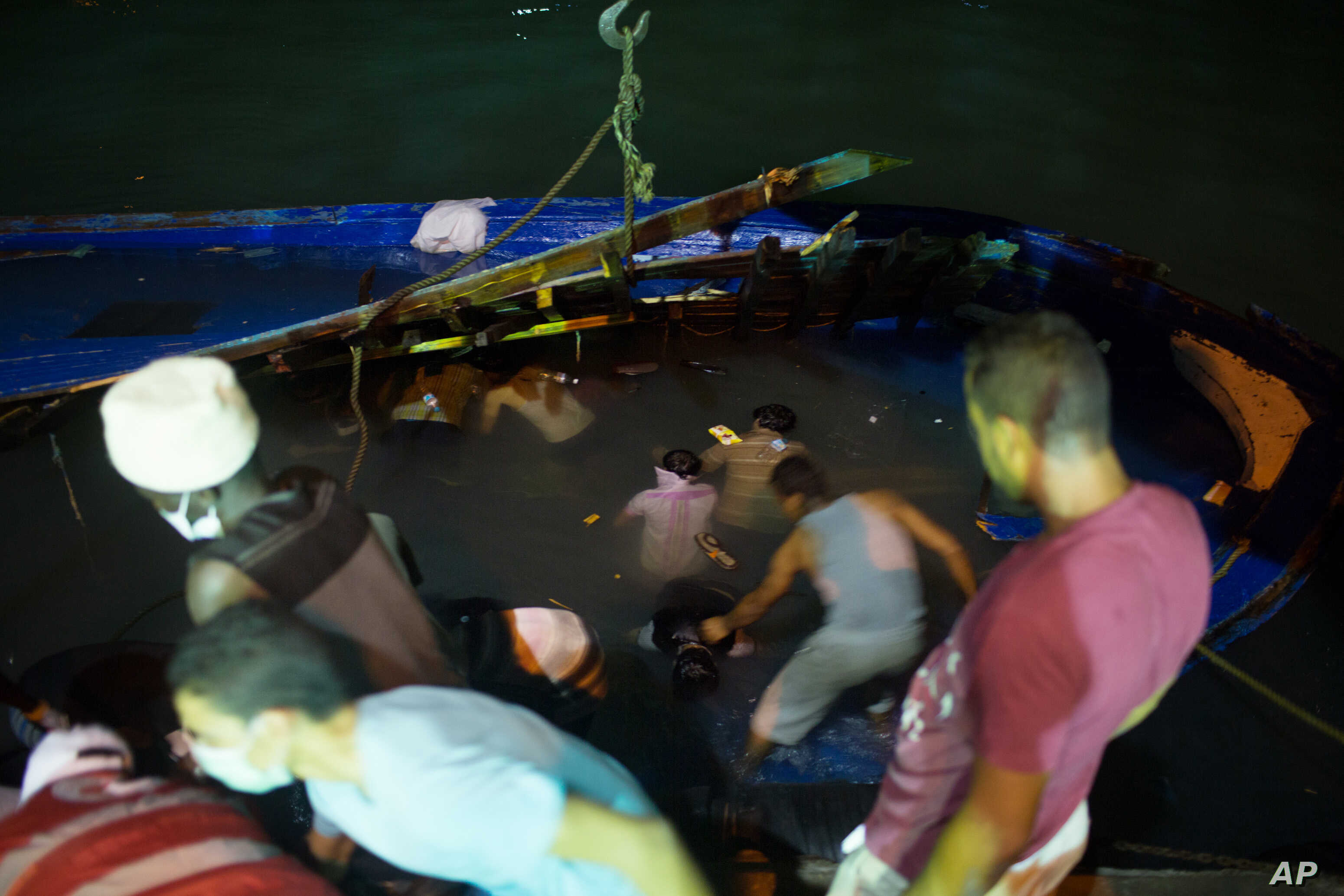 Rescuers work to help survivors and remove bodies of migrants trapped beneath the deck of a boat after it sank in the Mediterranean Sea off the coast of in Zuwara, Libya, Aug. 27, 2015.