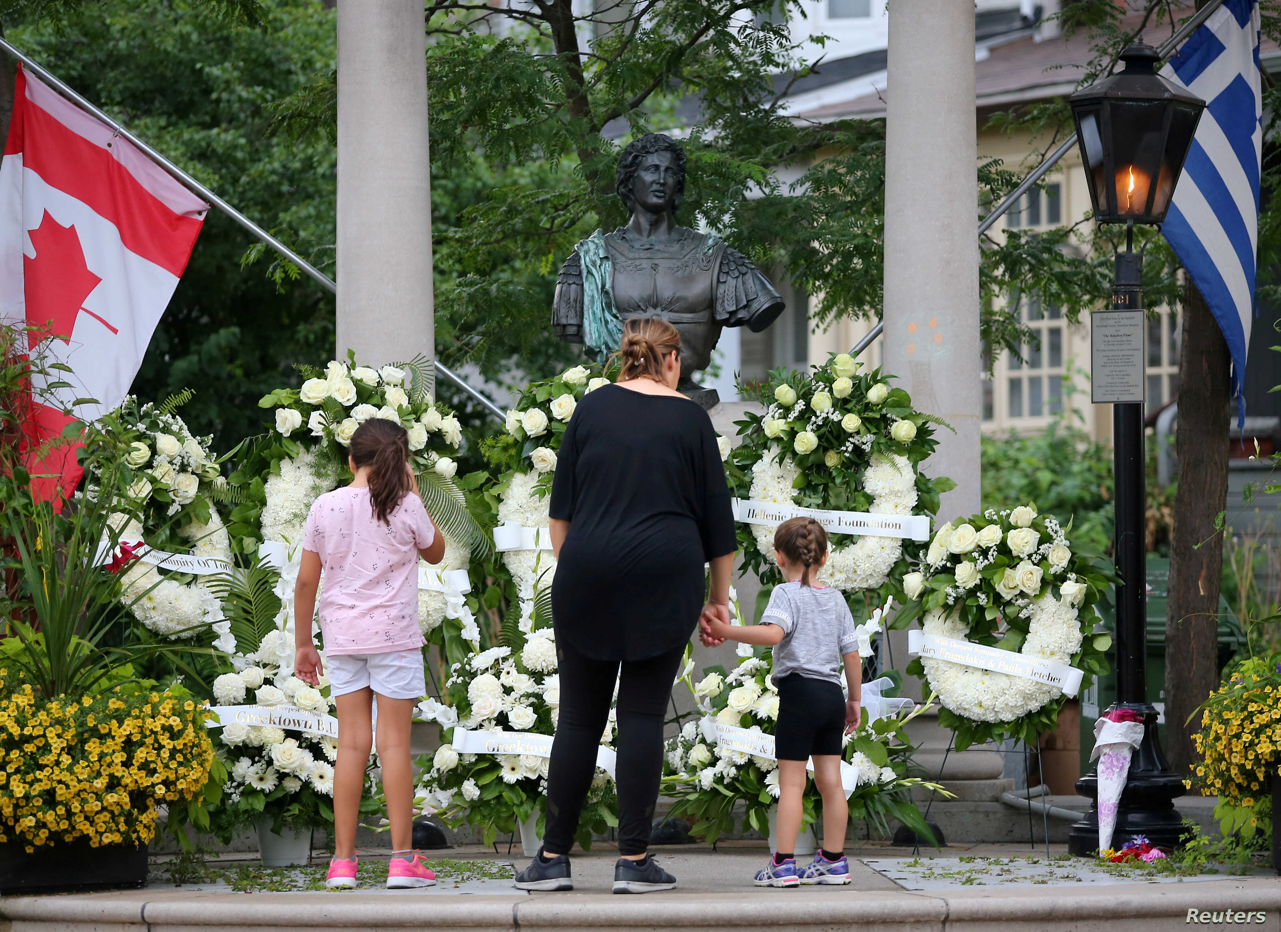 FILE - Canadian and Greek flags hang above memorial wreaths at Alexander the Great Parkette, the scene of a mass shooting on Danforth Avenue in Toronto, Ontario, Canada, July 24, 2018.