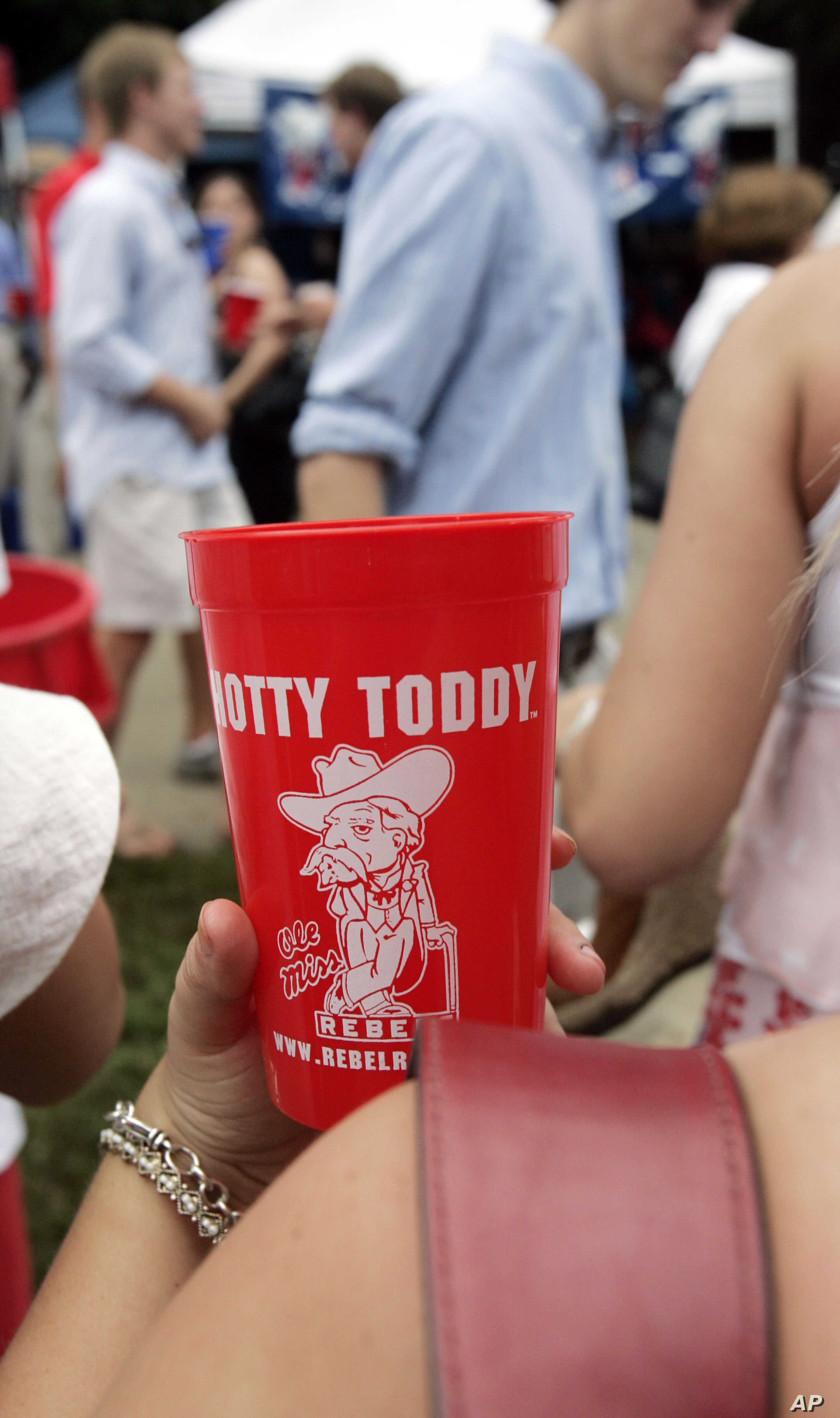 FILE - Health officials say open containers of food, shared cups of refreshment and lack of immediate hand sanitizing dispensers make tailgate gatherings, like this on at the University of Mississippi in Oxford, opportunities for students and fans to...