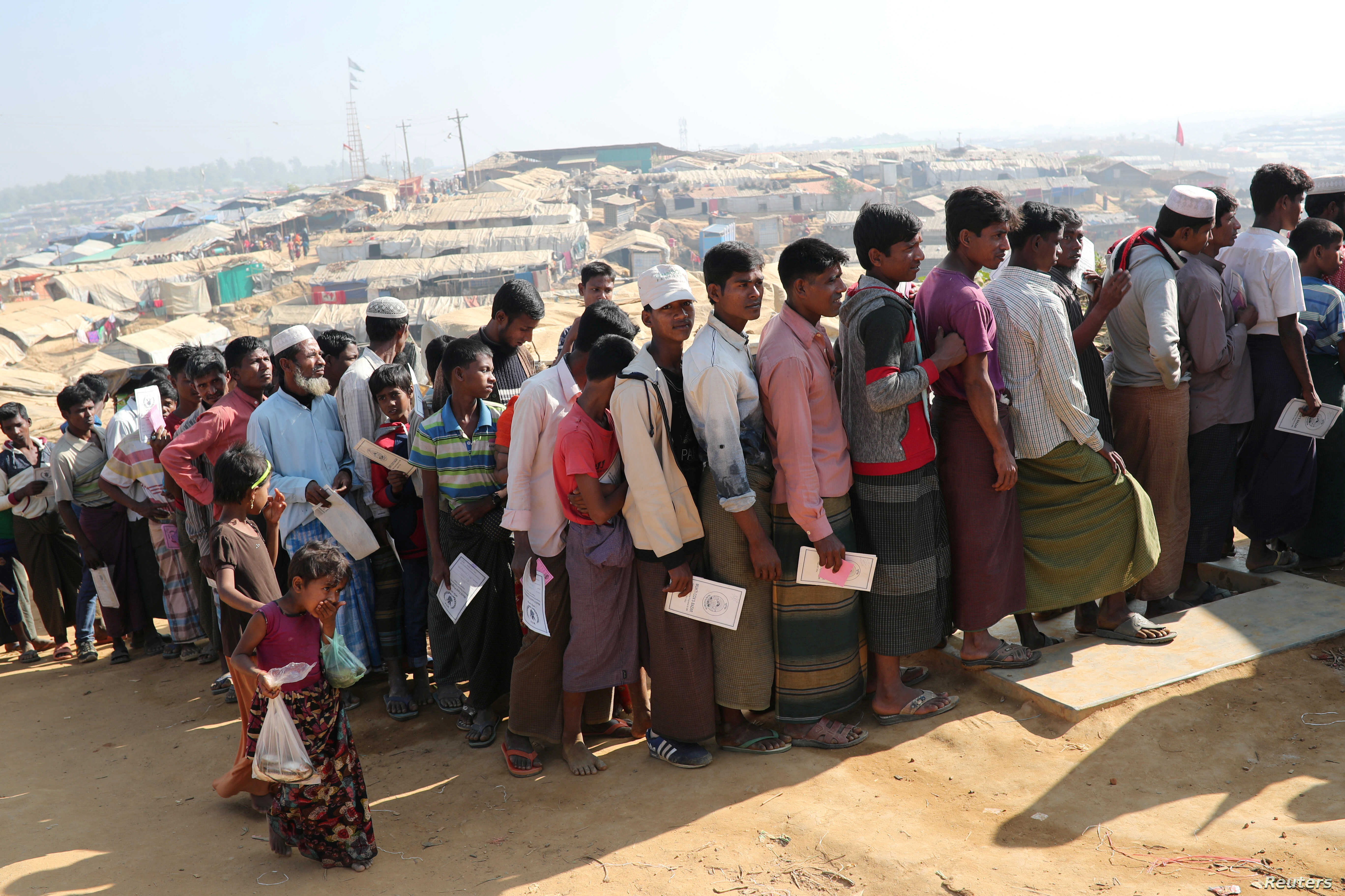 Rohingya refugees stand in a queue to collect aid supplies in Kutupalong refugee camp in Cox's Bazar, Bangladesh, Jan. 21, 2018.