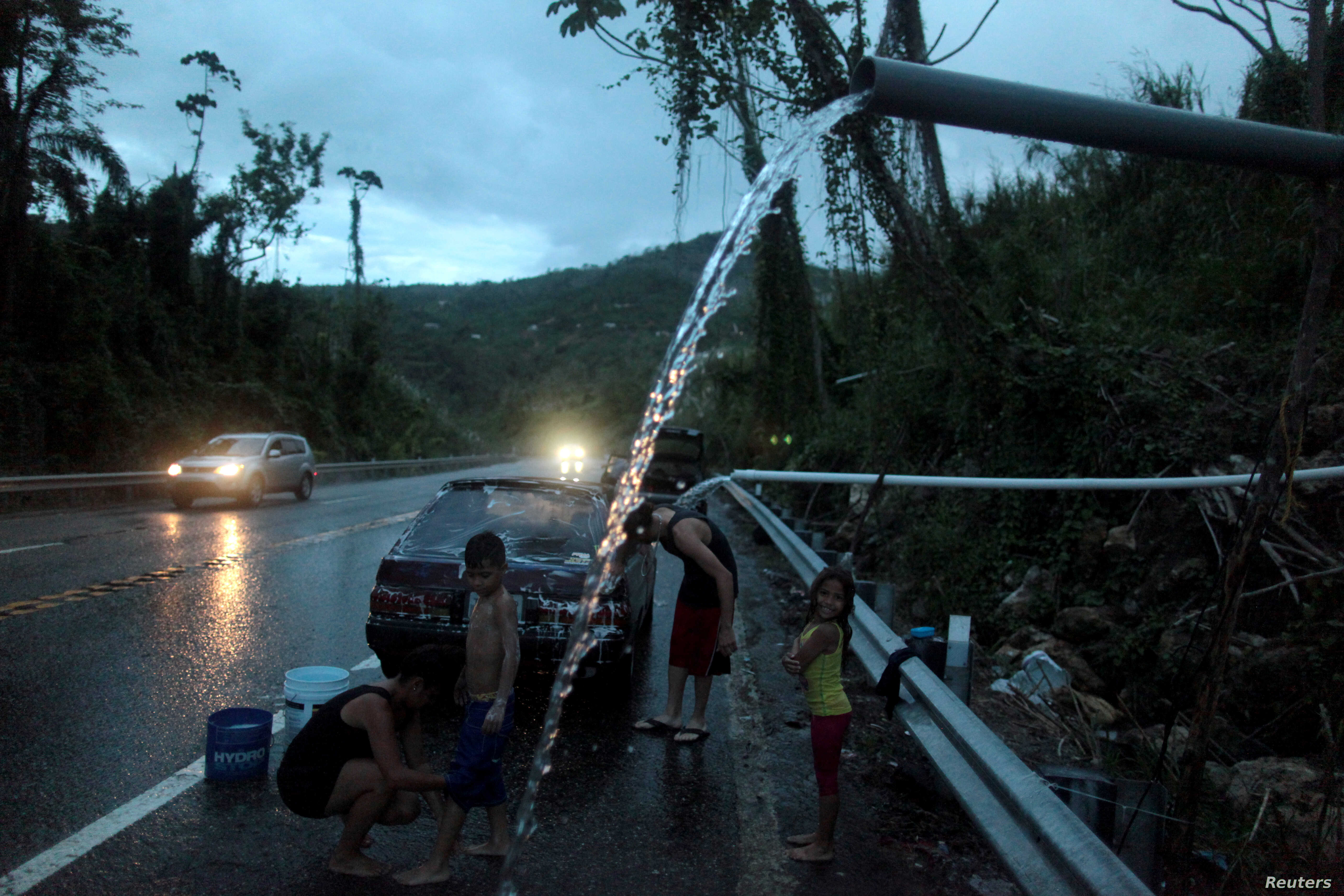 A family bathe and wash their car with mountain spring water in Utuado, Puerto Rico, Nov. 9, 2017, as the territory continues to deal with the aftermath of Hurricane Maria, which struck in September.
