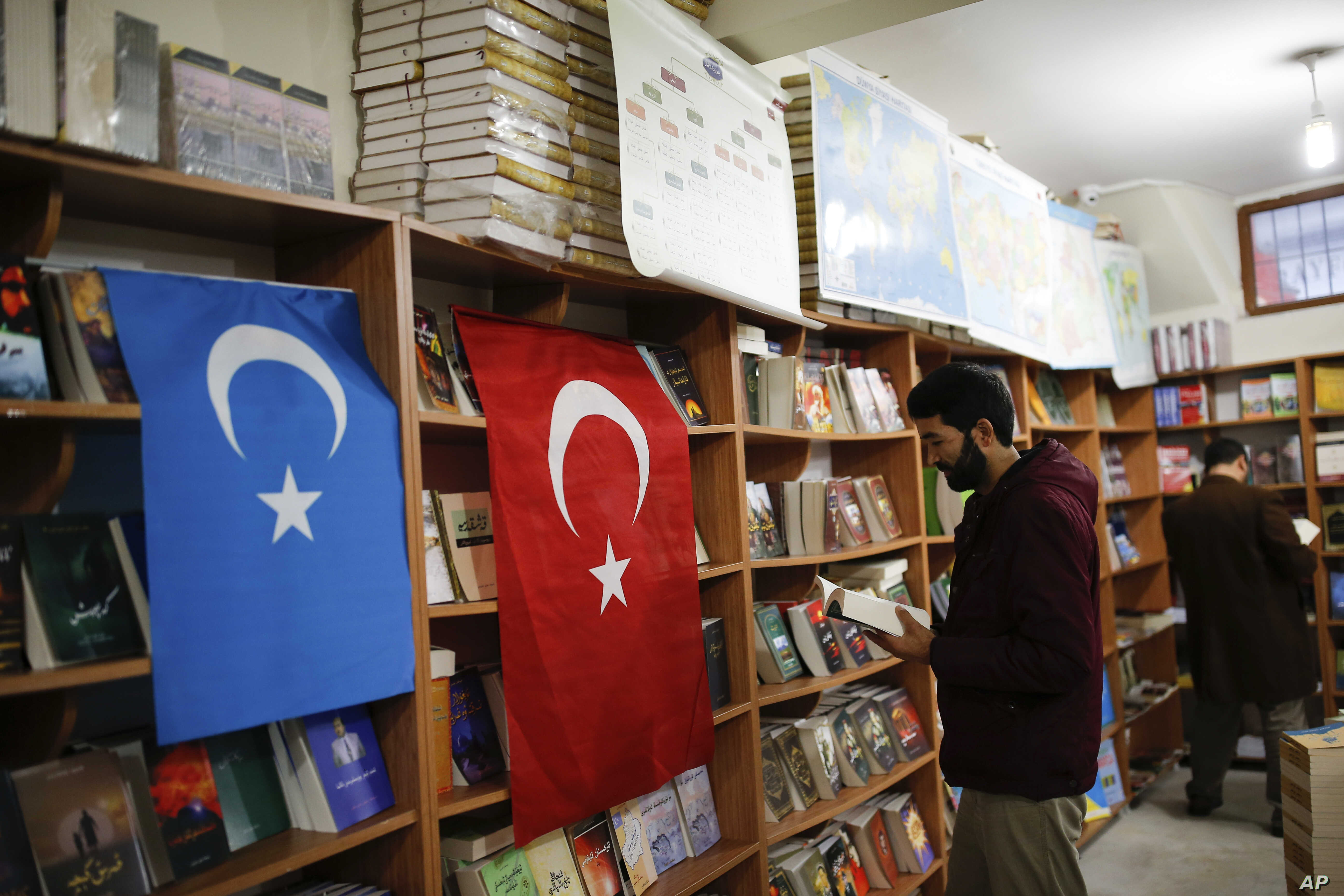 "A man reads a book in a bookstore where flags which represents Turkey and ""East Turkistan,"" the name Uighurs who oppose Chinese rule call their homeland, are hung in Istanbul's Zeytinburnu neighborhood, Dec. 14, 2017."