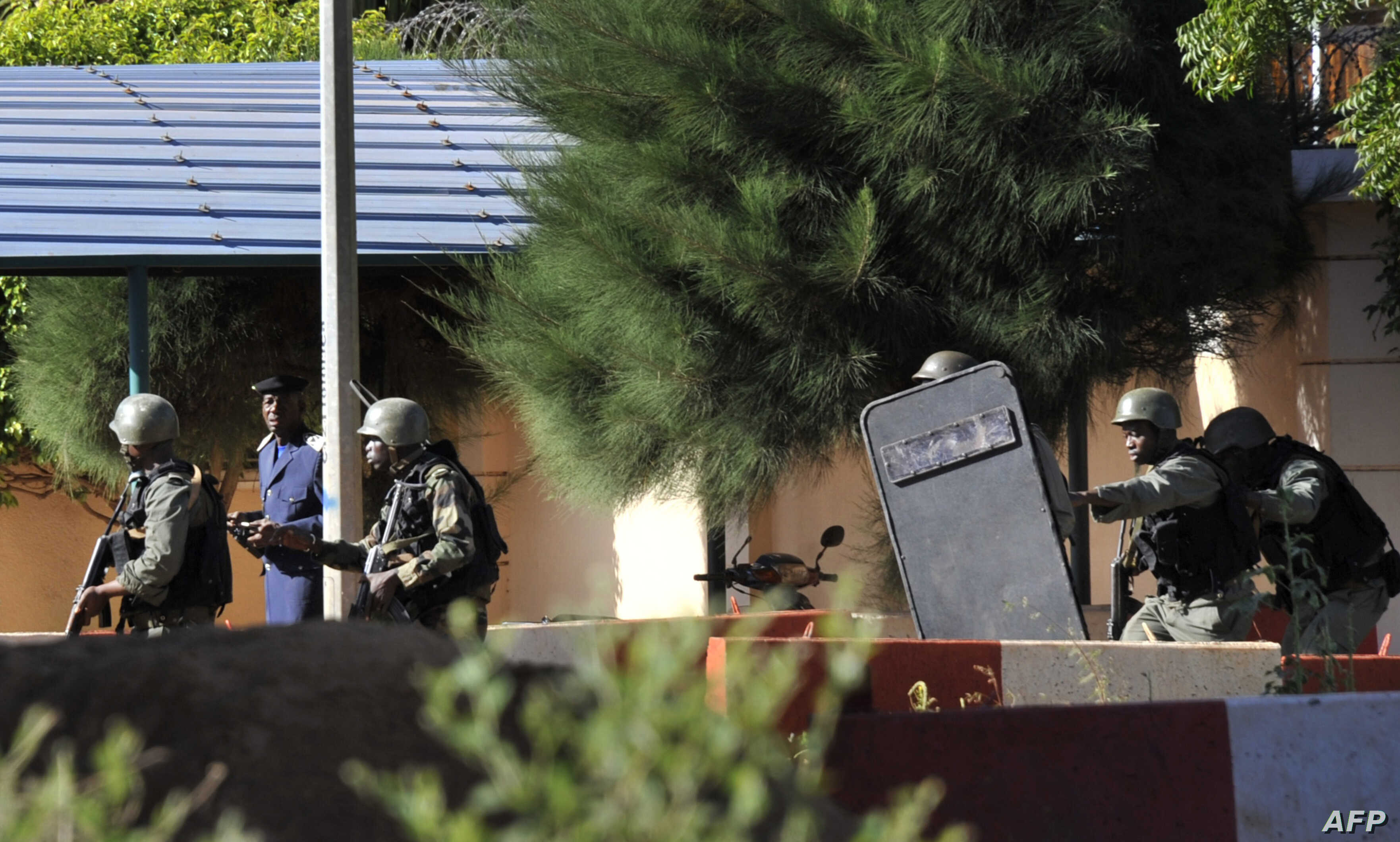 Malian troops take position outside the Radisson Blu hotel in Bamako on November 20, 2015. Gunmen attacked the luxury hotel in Mali's capital Bamako, seizing 170 guests and staff in an ongoing hostage situation that has left at least three people dea...