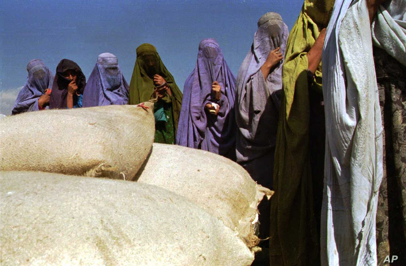 FILE - A group of women wearing burqas, most of them widows, await food aid at a distribution center run by the International Committee of the Red Cross in Kabul, Afghanistan, Oct. 13, 1996.