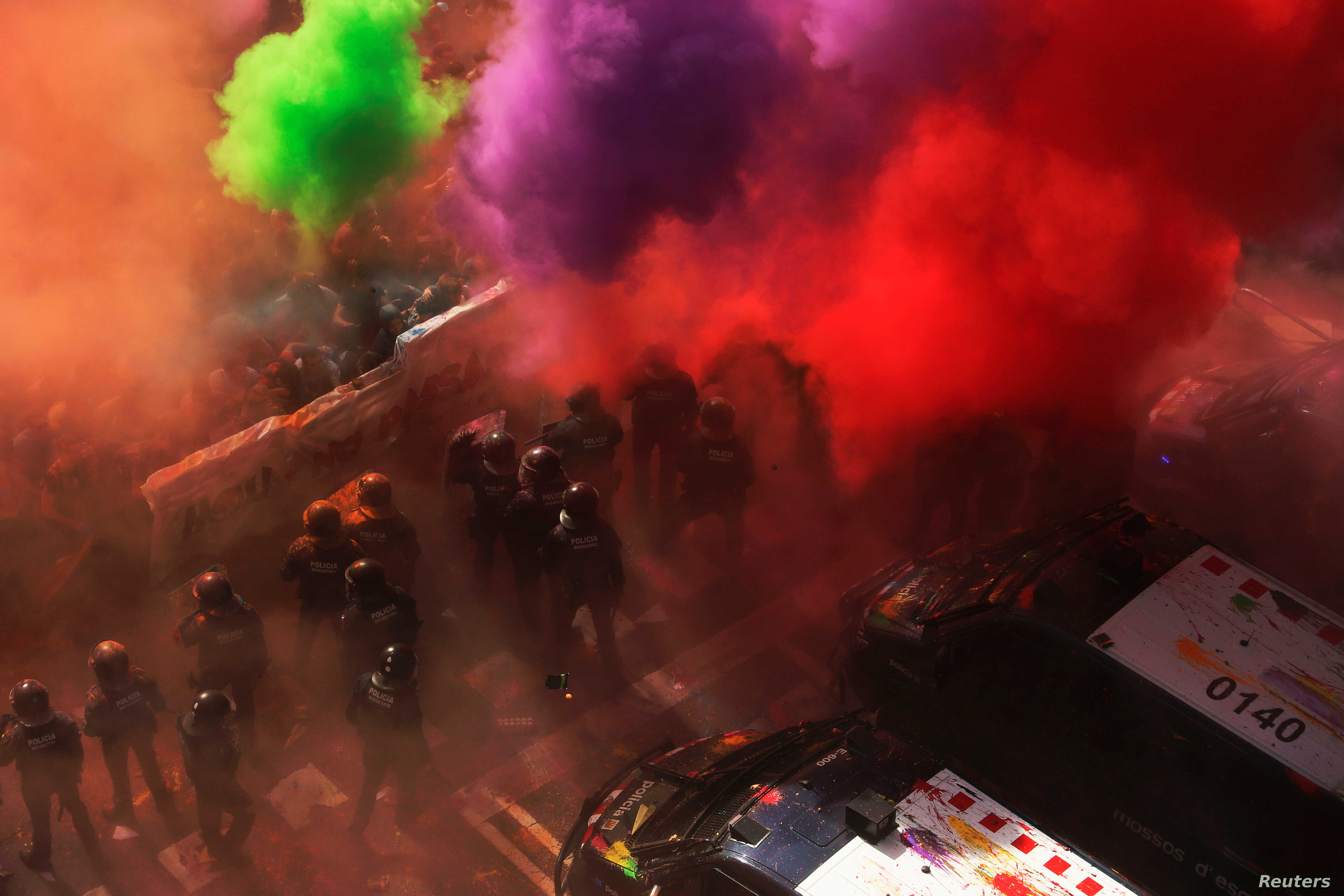 Separatist protesters throw colored powder toward Mossos d'Esquadra police officers in Barcelona, Spain, Sept. 29, 2018, as they protest against a demonstration in support of the Spanish police units who took part in the operation to prevent an indep...