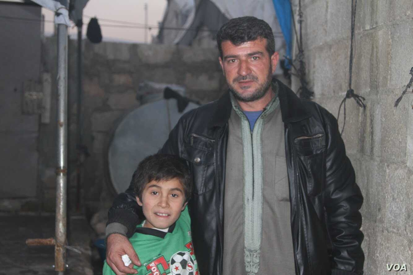 Hoger, a Yazidi boy taken by IS with his mother and siblings from Sinjar in 2014, stands beside his orphanage housefather Rami Qaddor in Atmeh camp for refugees in northern Syria.