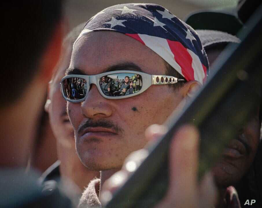 FILE – Sunglasses worn by an Americans gang member reflect the scene of a drug raid in Valhalla Park, a neighborhood in Cape Town, South Africa, Aug. 14, 1996. The notorious gang has been entrenched for decades. (AP)