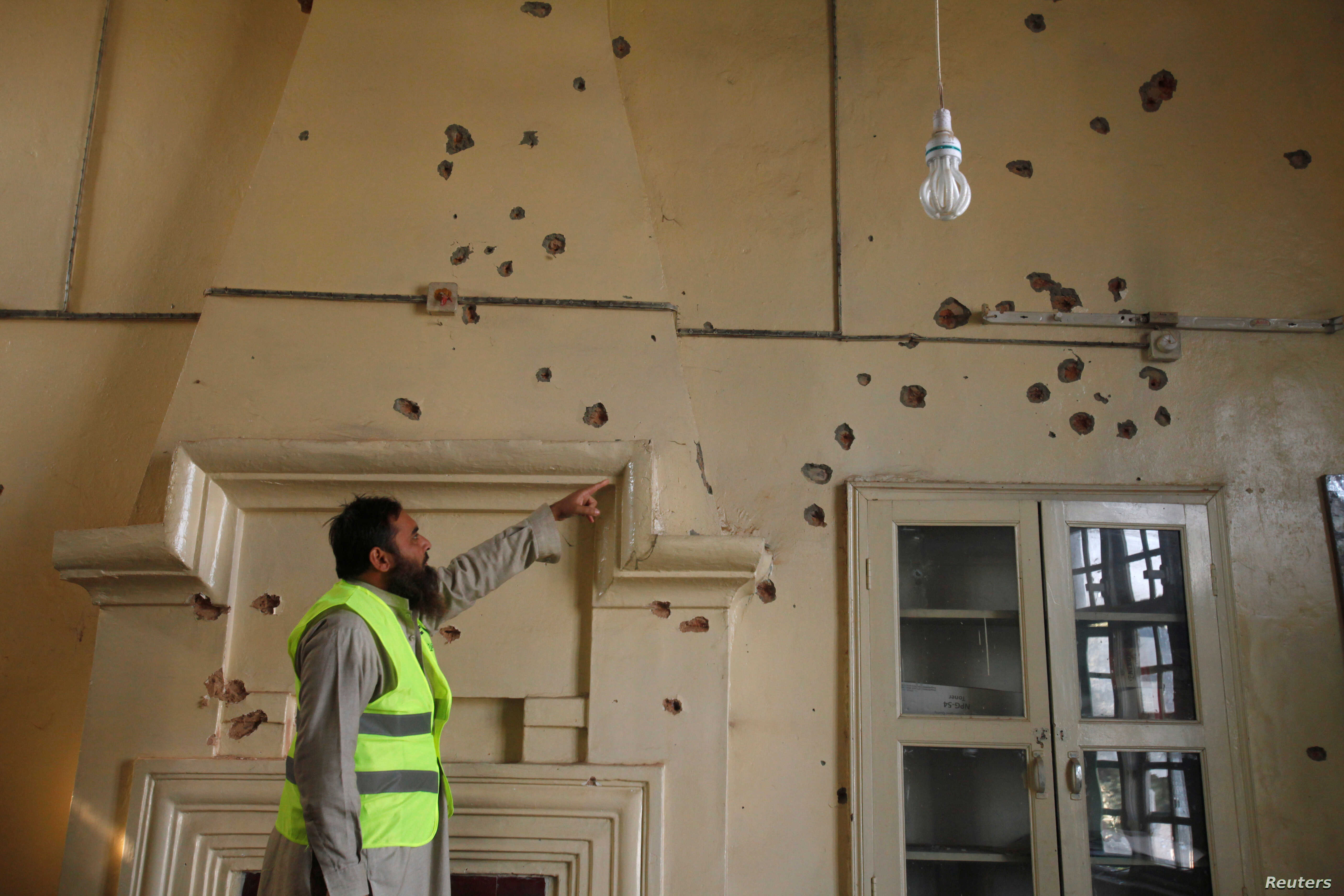 A rescue worker points to bullet holes in the wall of a computer lab after the shooting at Directorate of Agriculture Institute in Peshawar, Pakistan, Dec. 1, 2017.