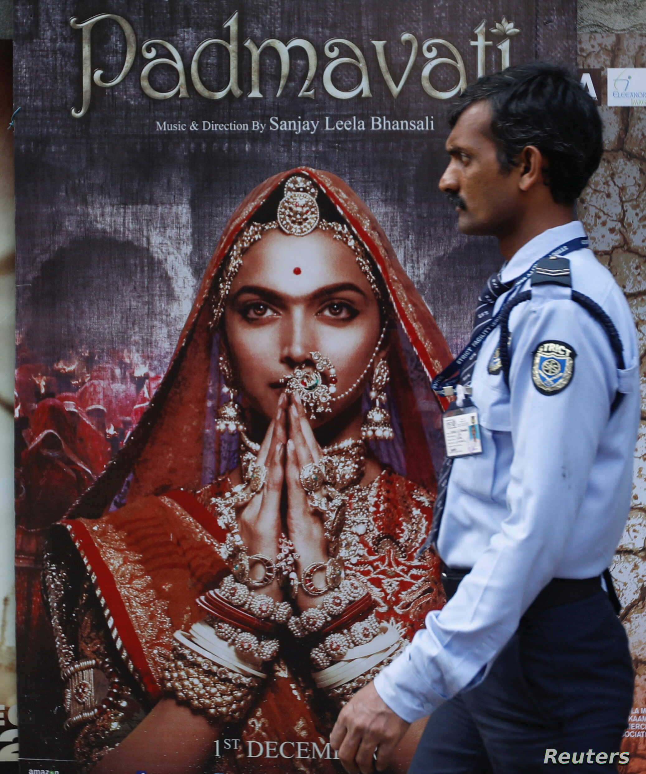 """A security guard walks past a poster of the upcoming Bollywood movie """"Padmavati"""" outside a theater in Mumbai, India, Nov. 21, 2017."""